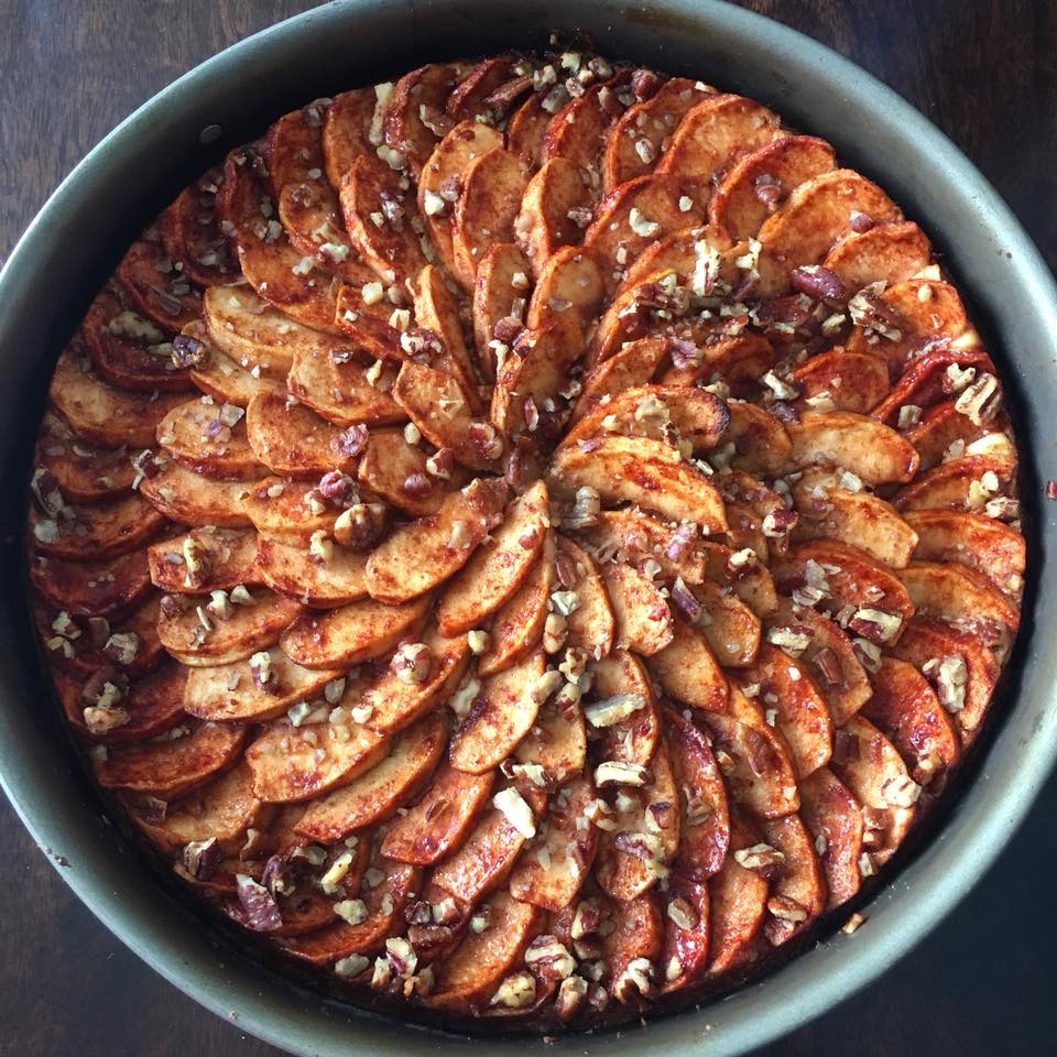 cheesecake topped with apples and pecans in a springform pan