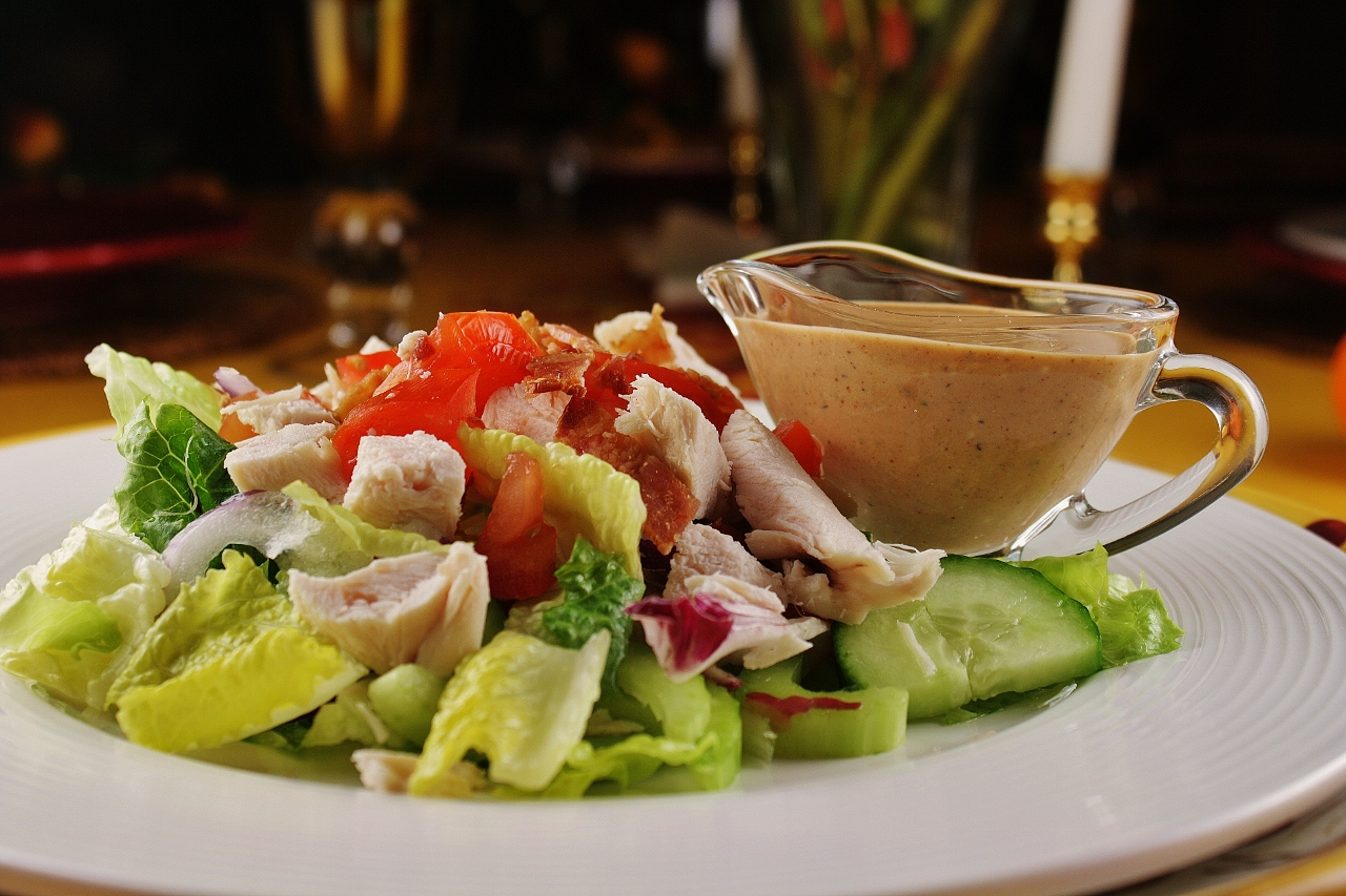 a plate of salad greens topped with chopped chicken breast, tomatoes, cucumber, and crumbled bacon with a glass pitcher of salad dressing on the side