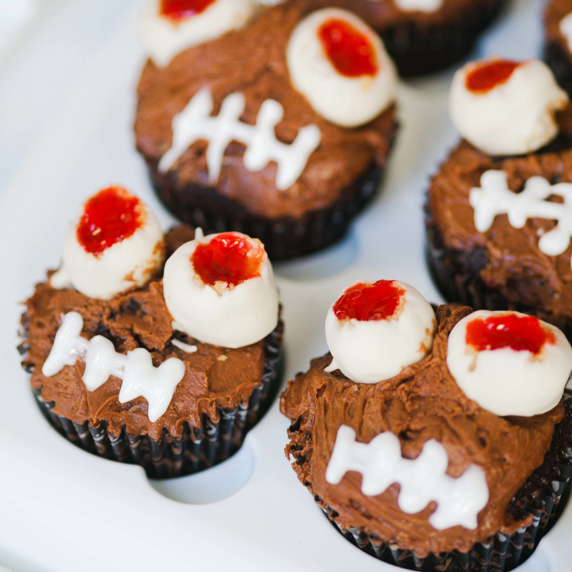 chocolate frosted cupcakes with monster eyes and mouth