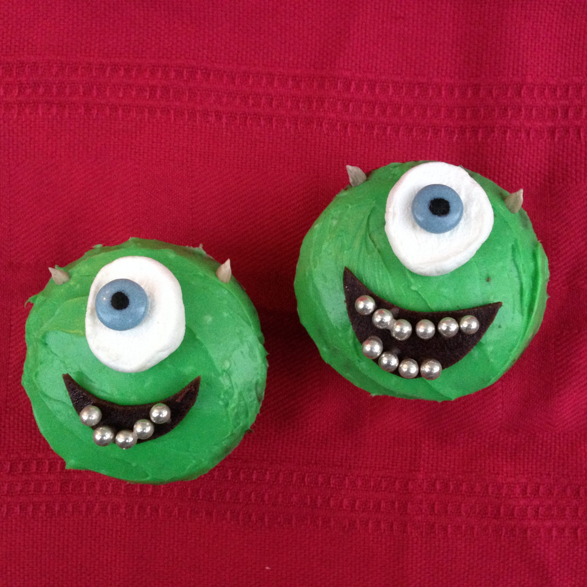 two green frosted cupcakes with cyclops eyes