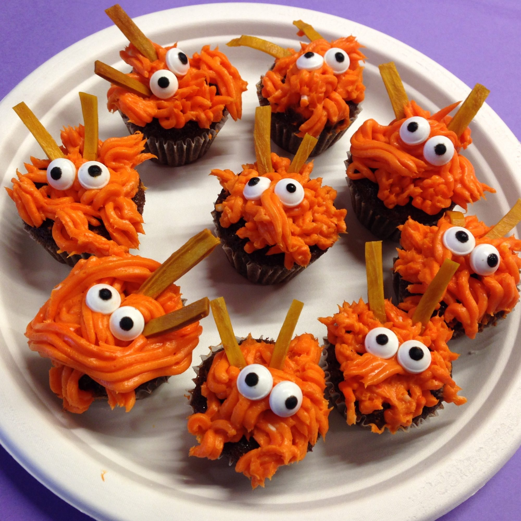 orange frosted cupcakes with monster faces