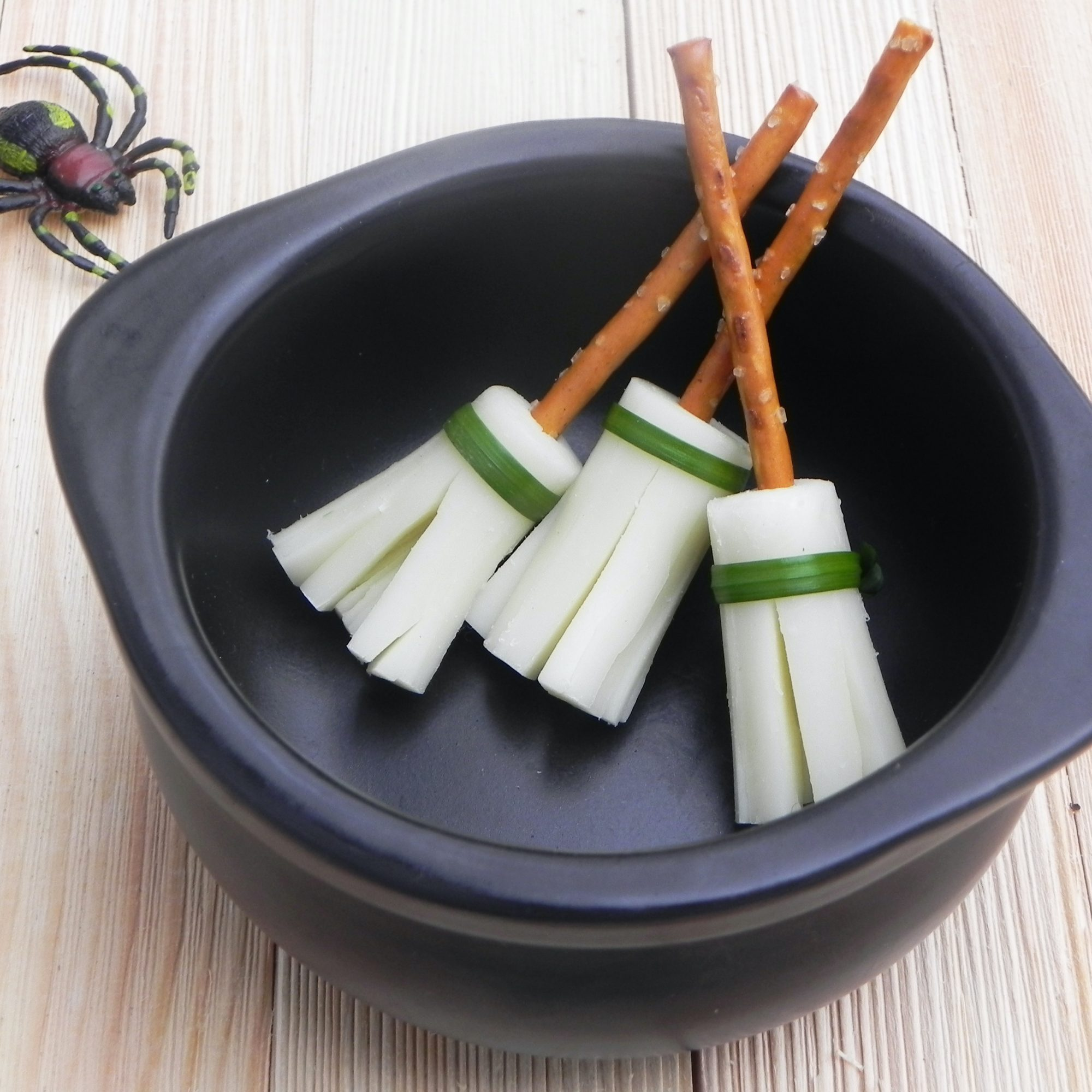 string cheese and pretzel broomsticks in a black bowl