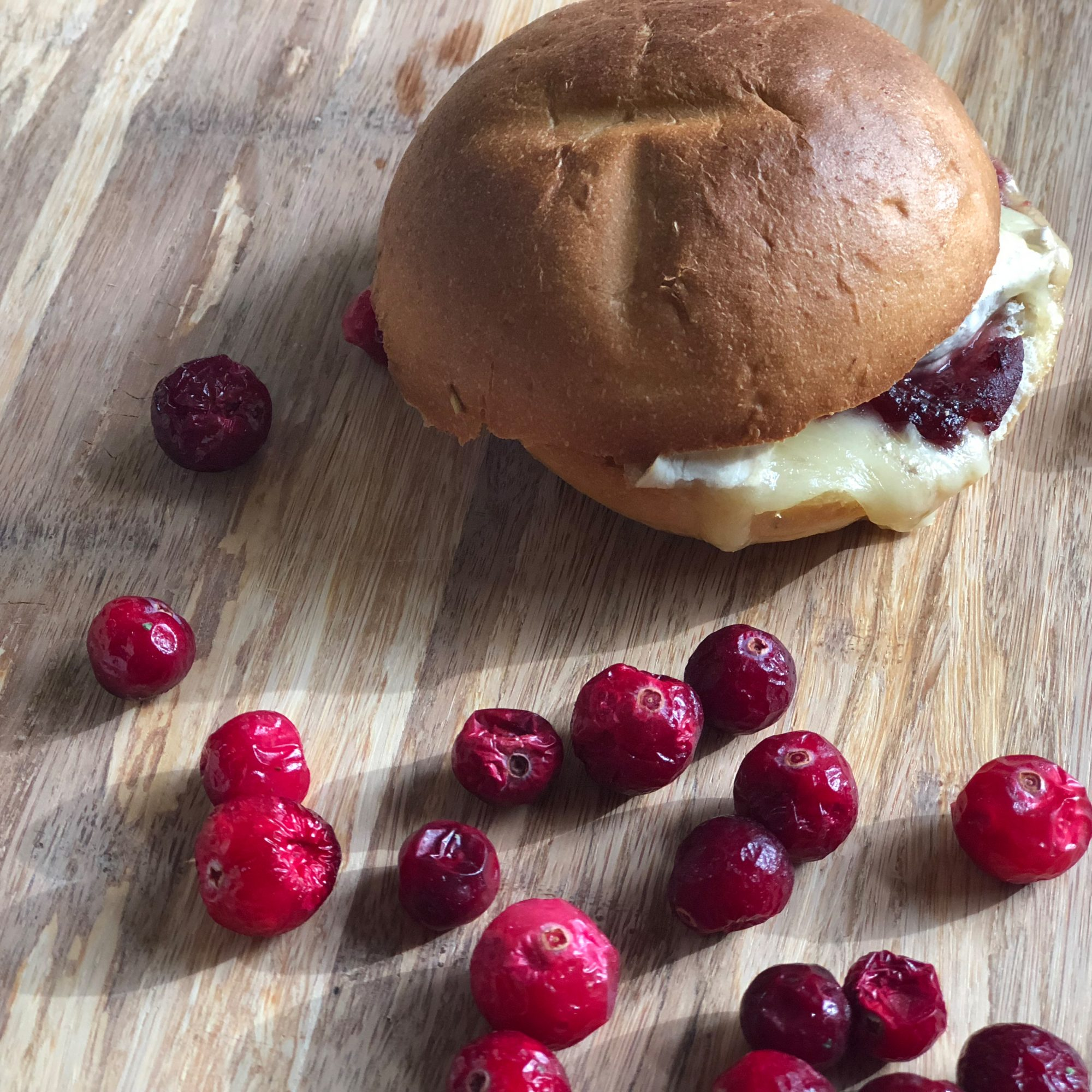 Vegetarian Brie and Cranberry Paninis on a wooden background