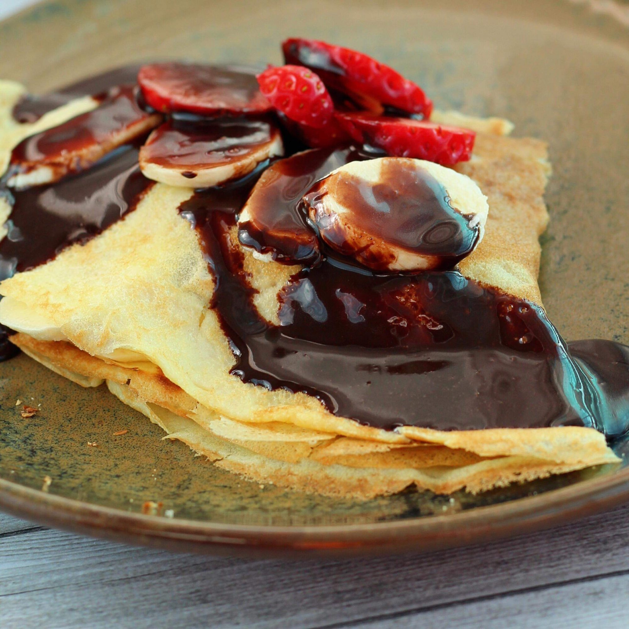 a plate of triangular crepes drizzled with chocolate sauce and topped with strawberry and banana slices