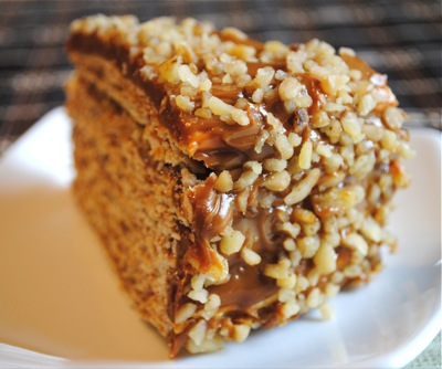 side view of a slice of 10-layer cake frosted with dulce de leche and coated with chopped walnuts