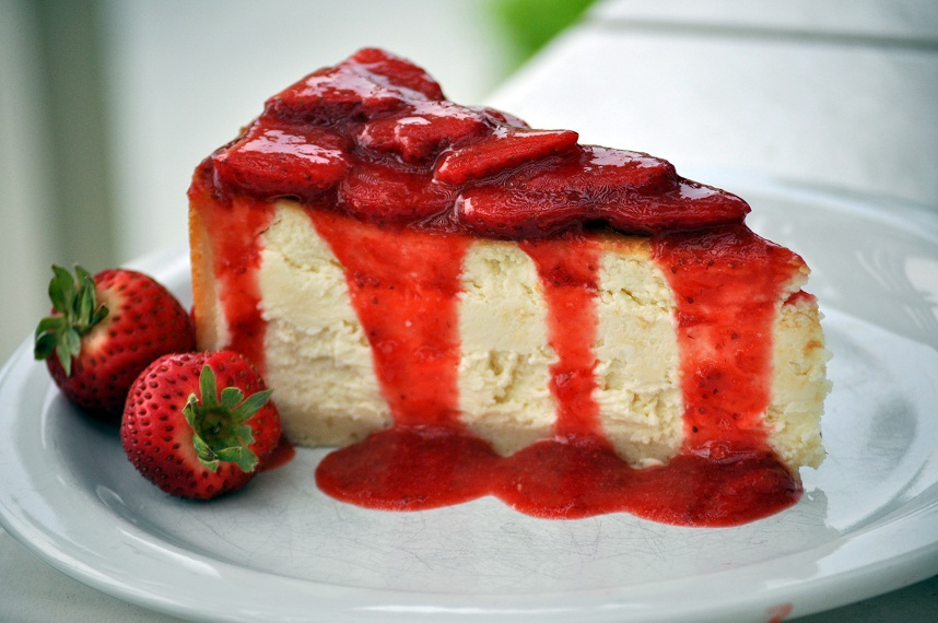 side view of a slice of plain cheesecake topped with bright red strawberry sauce, garnished with fresh strawberries