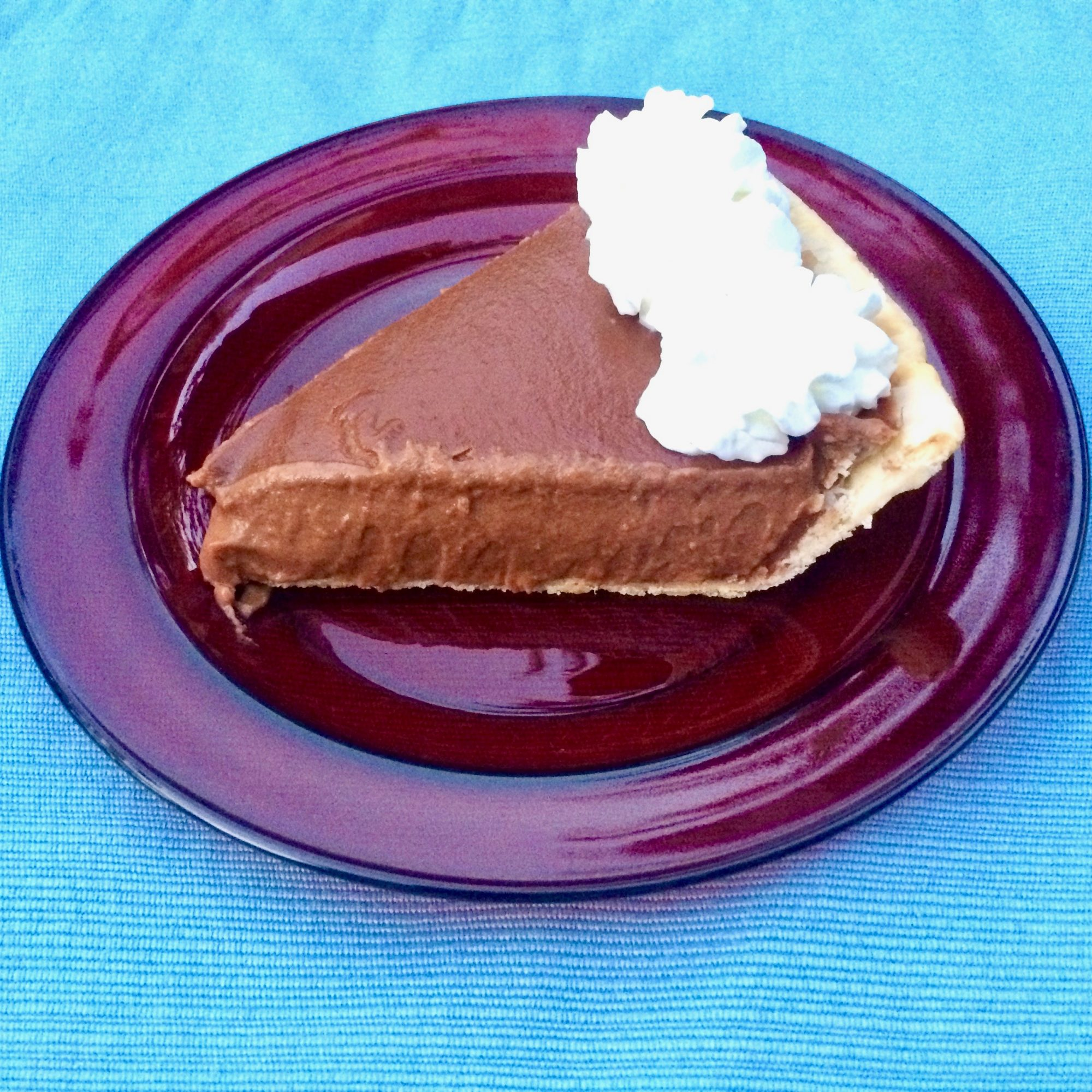 Slice of chocolate pumpkin pudding pie with whipped cream