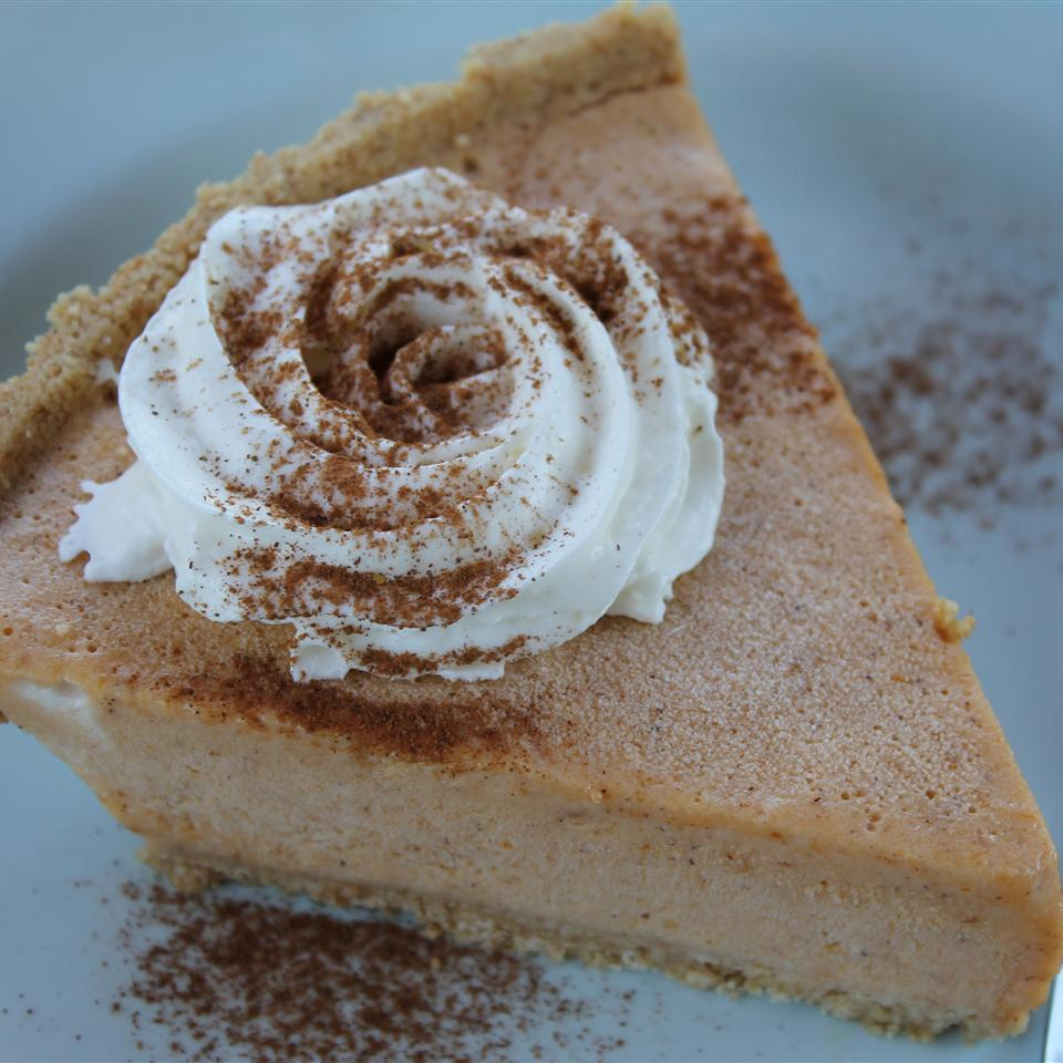 Frozen pumpkin pie with whipped cream and cinnamon sprinkled on top