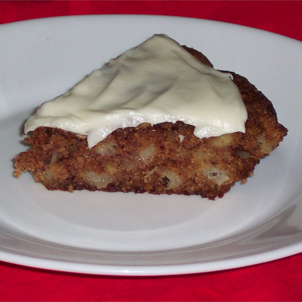 Apple pie with cream cheese frosting on white plate