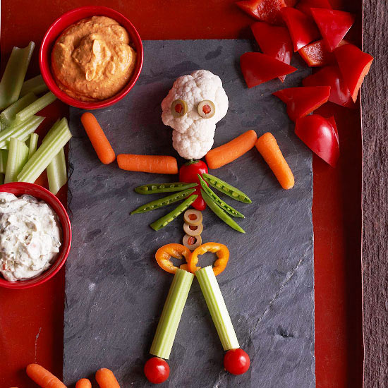 vegetables on a serving board in the shape of a skeleton served with hummus and creamy dip