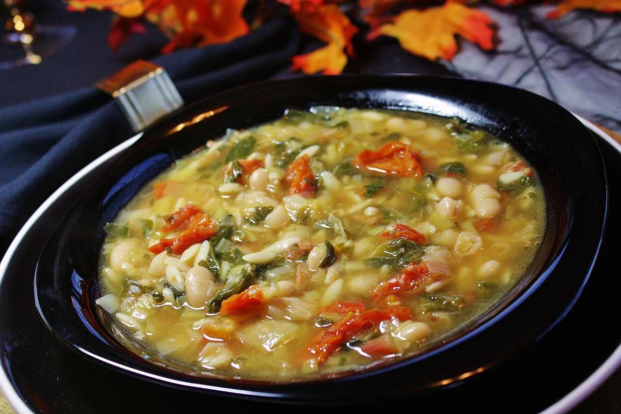 a shallow black soup bowl filled with a colorful white bean soup with a yellow broth, chopped tomatoes, and chard greens