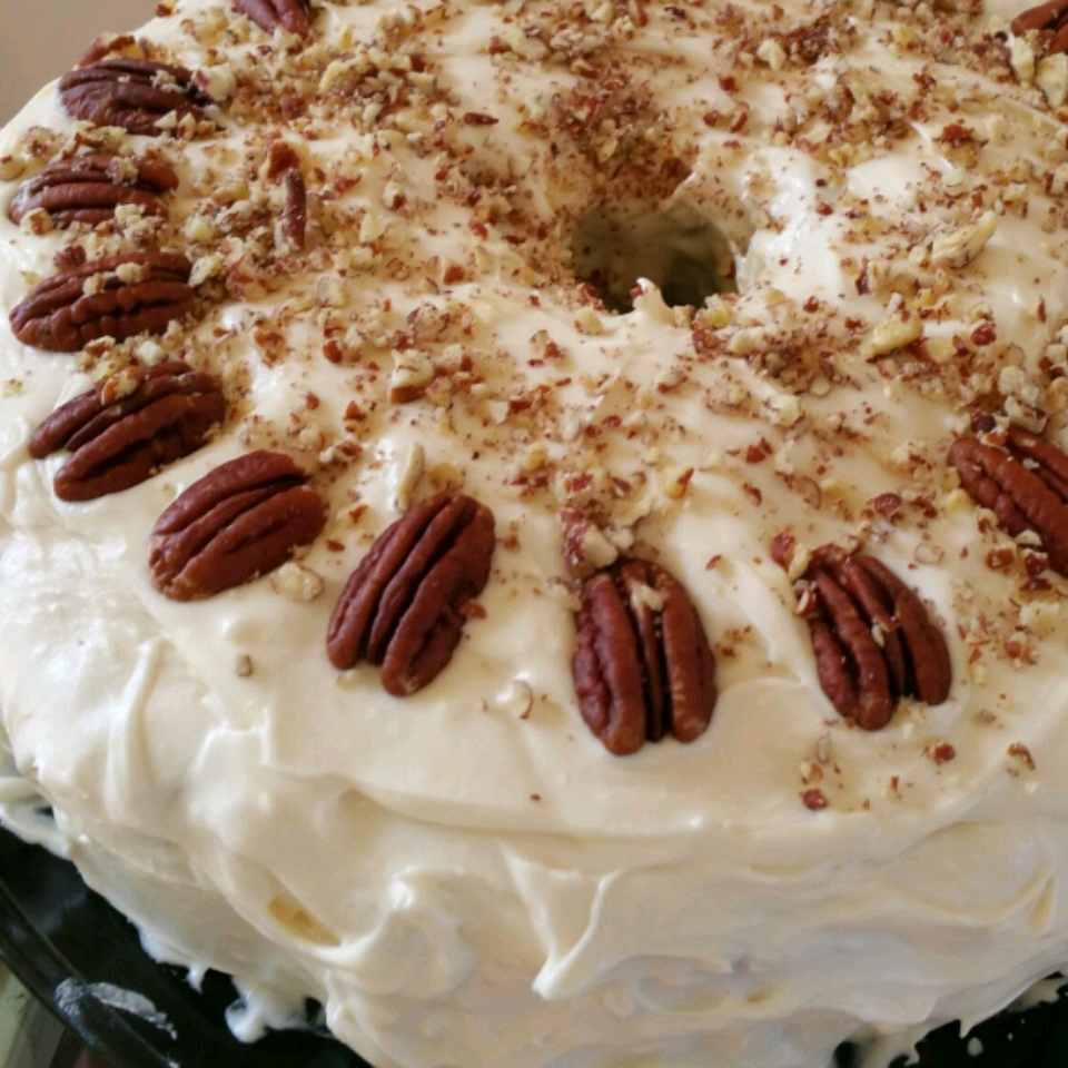 Hummingbird Cake topped with whole and chopped pecans