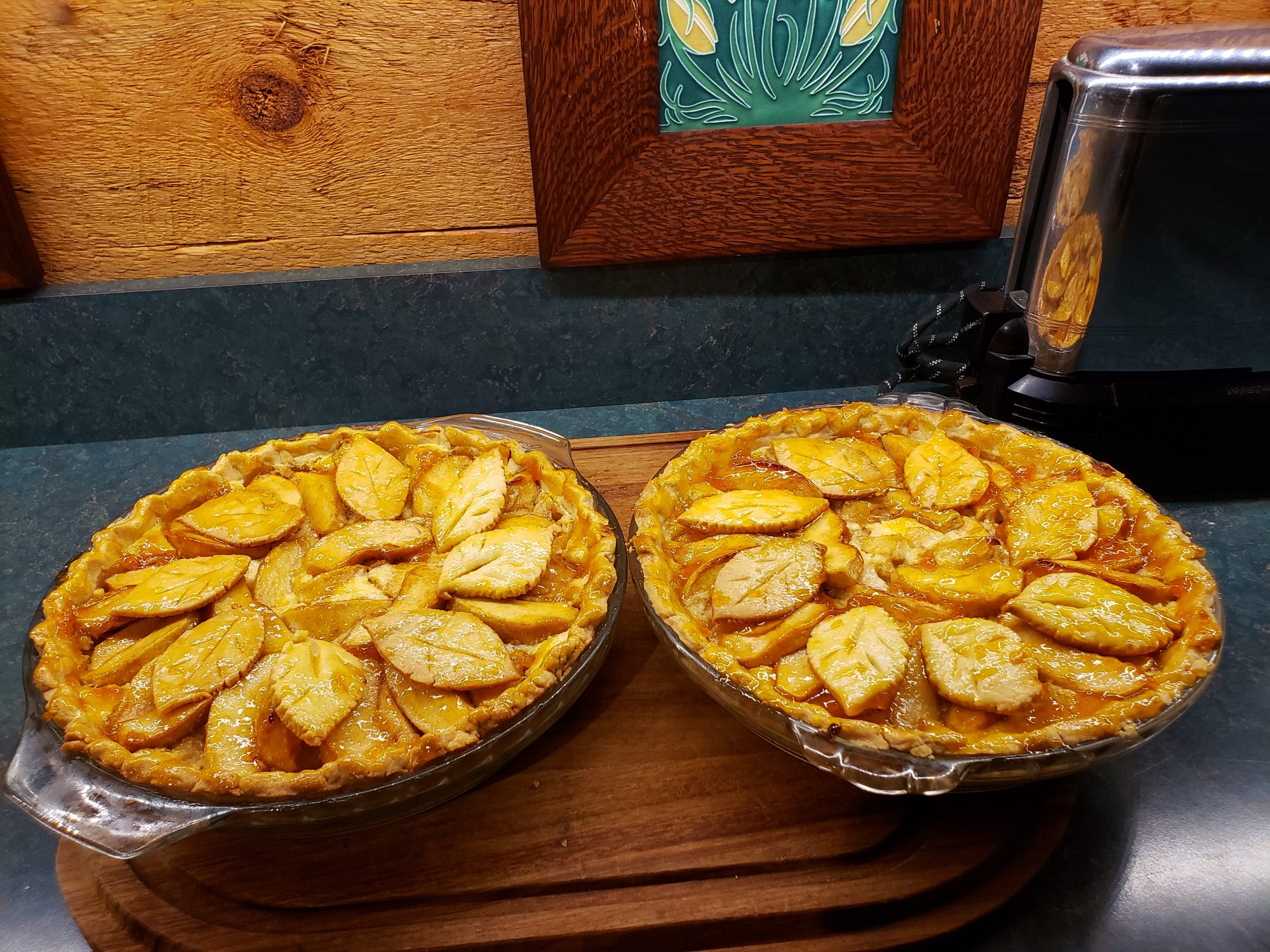 two apple pies garnished with leaf pastry cutouts