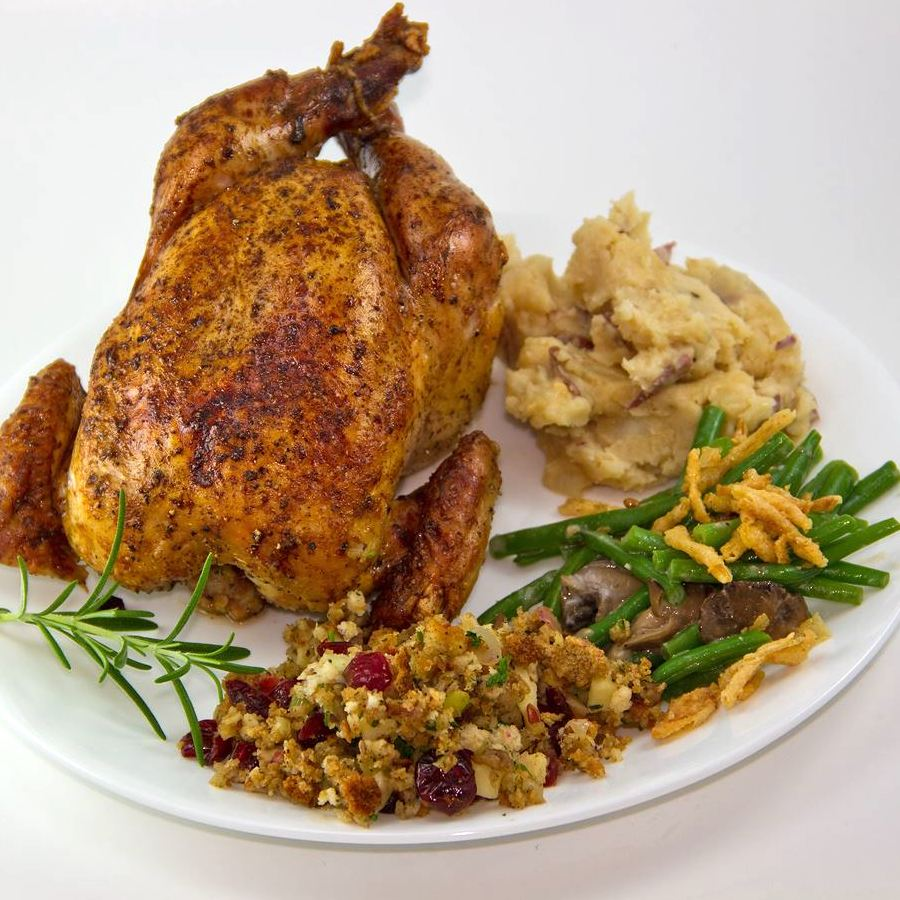 whole Cornish Game Hen on a plate with Thanksgiving sides