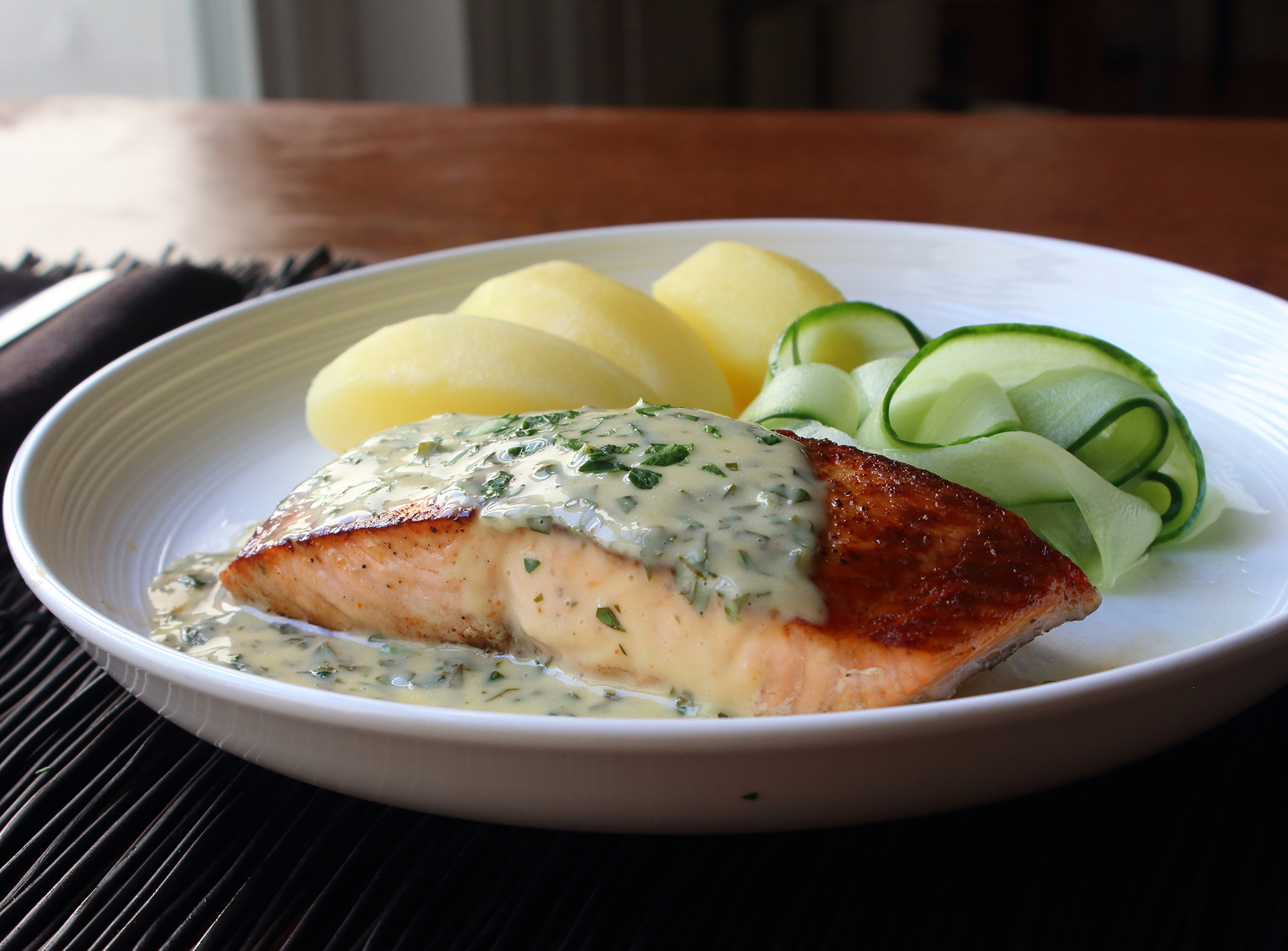 a white dinner plate showing a salmon fillet topped with butter sauce in the foreground, with boiled potatoes and shaved cucumber in the background
