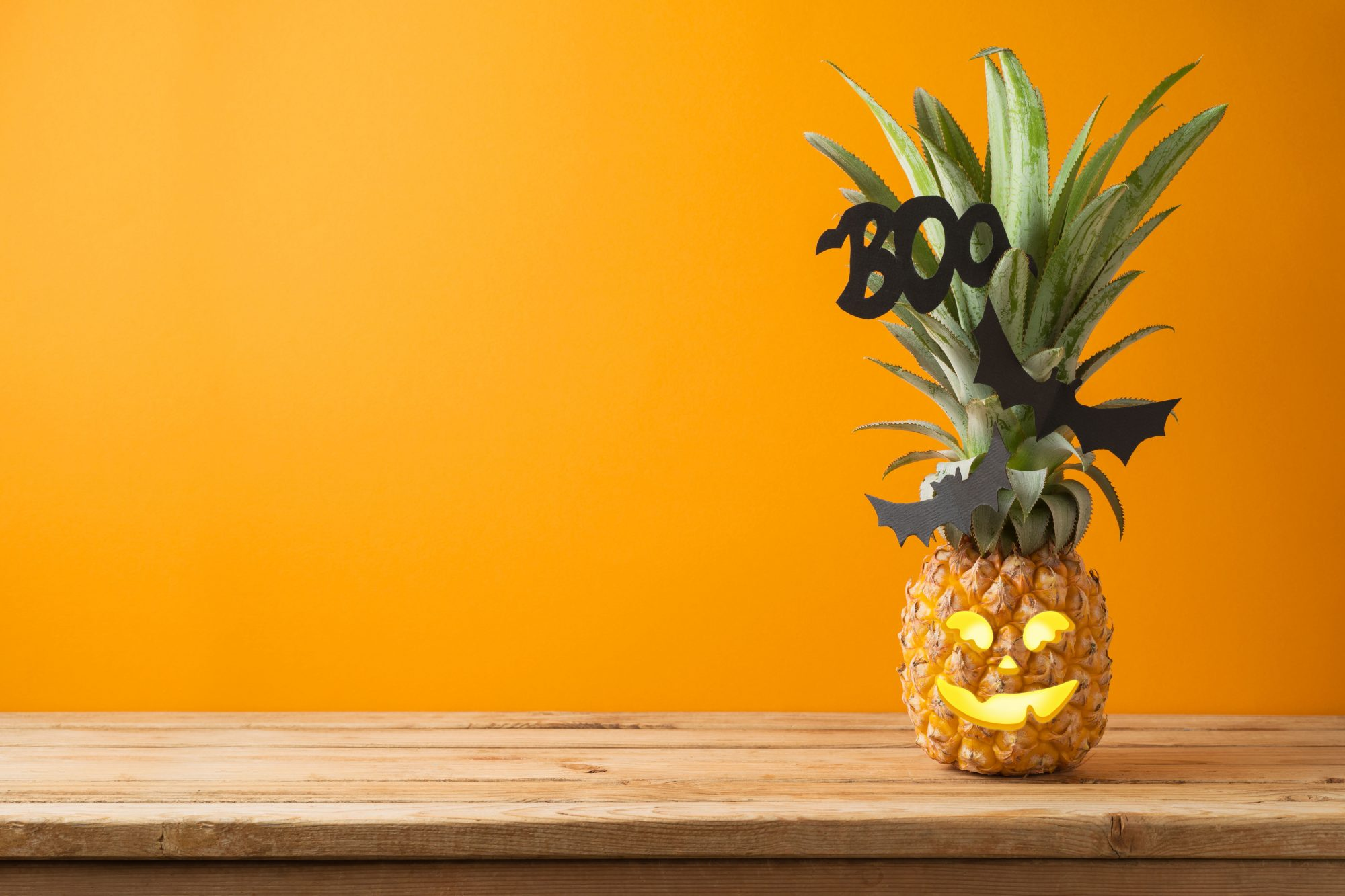 Pineapple jack o lantern on orange background with wooden table