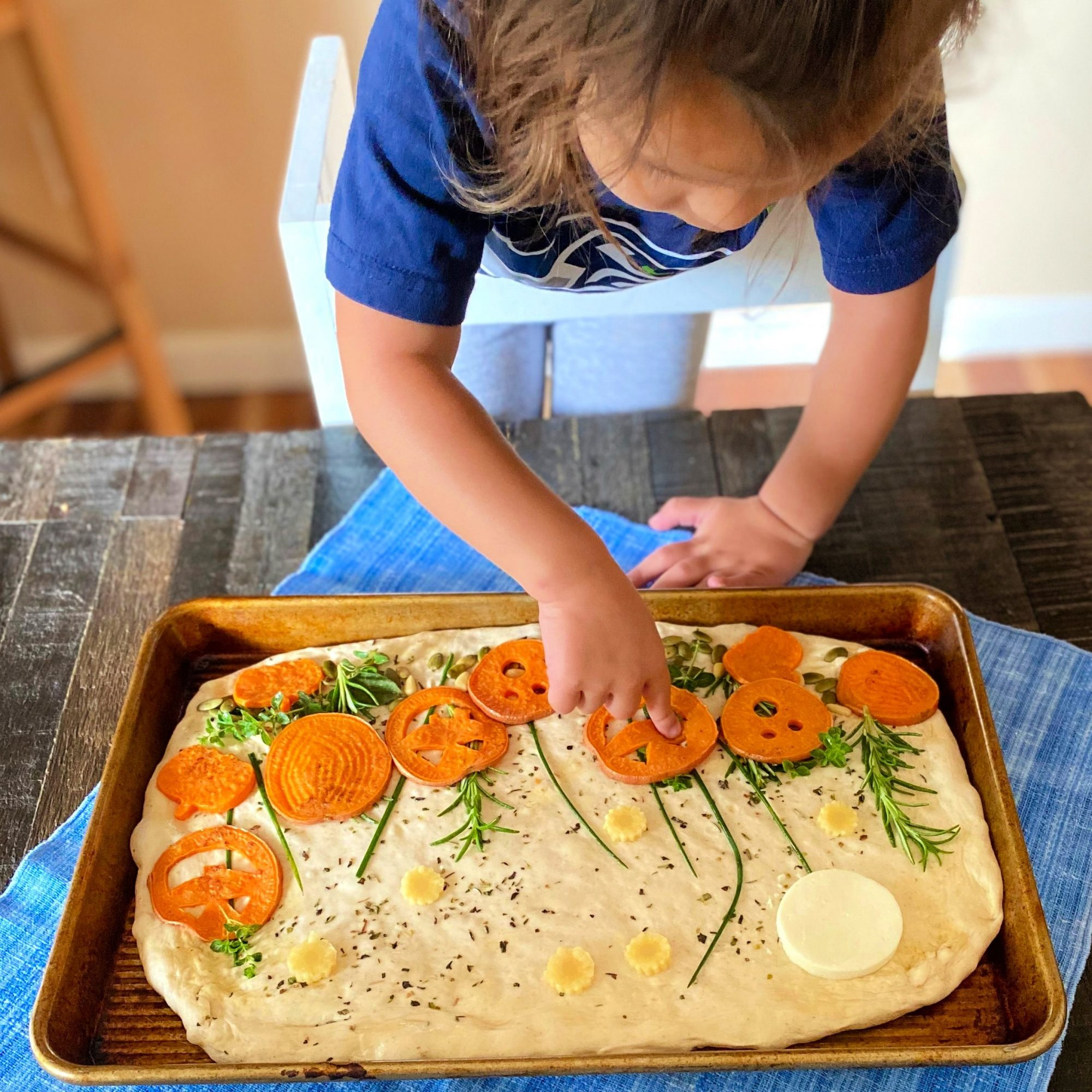 child decorating pumpkin patch focaccia with yam pumpkin faces and herbs