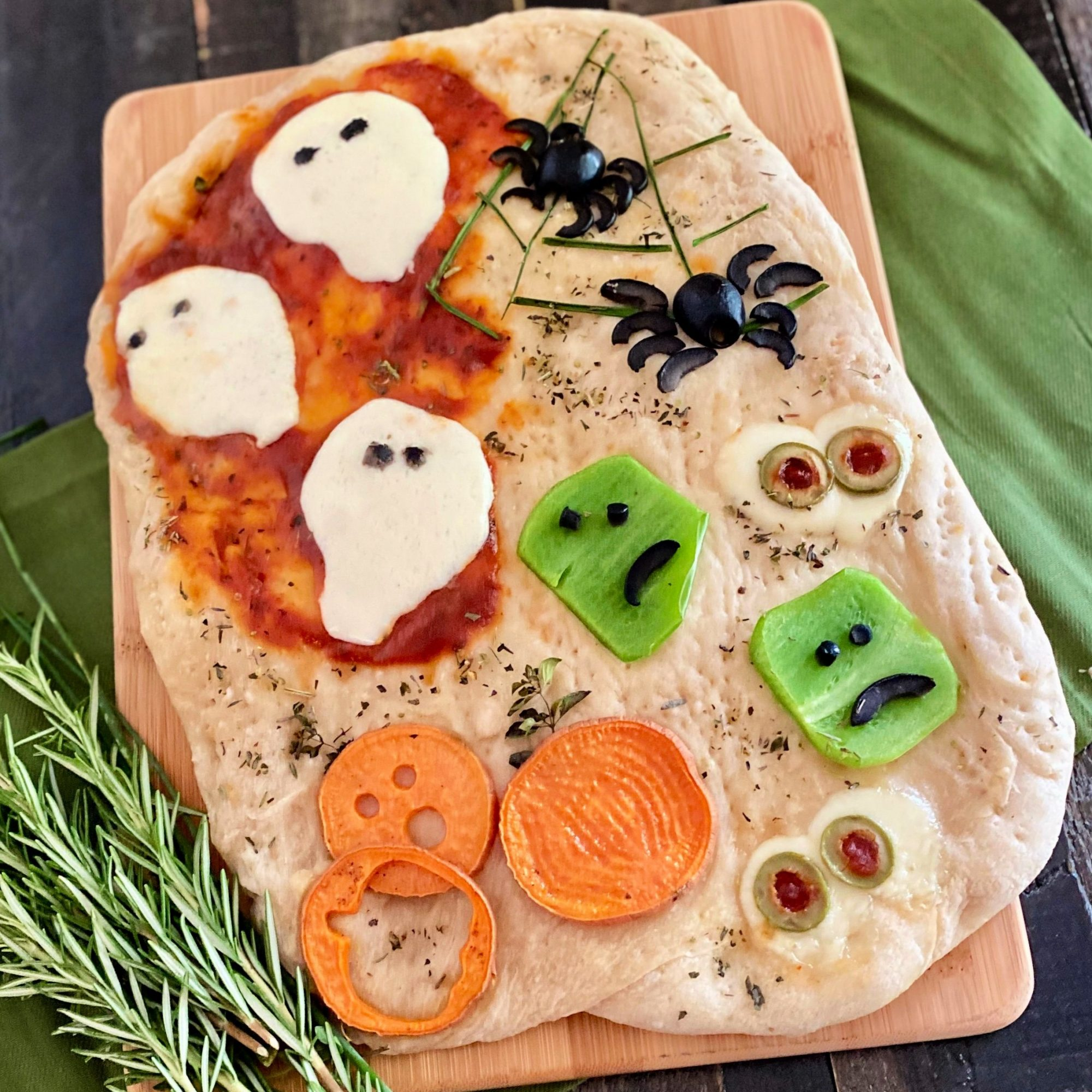 focaccia bread decorated with cheese ghosts, yam pumpkins, and black olive spiders
