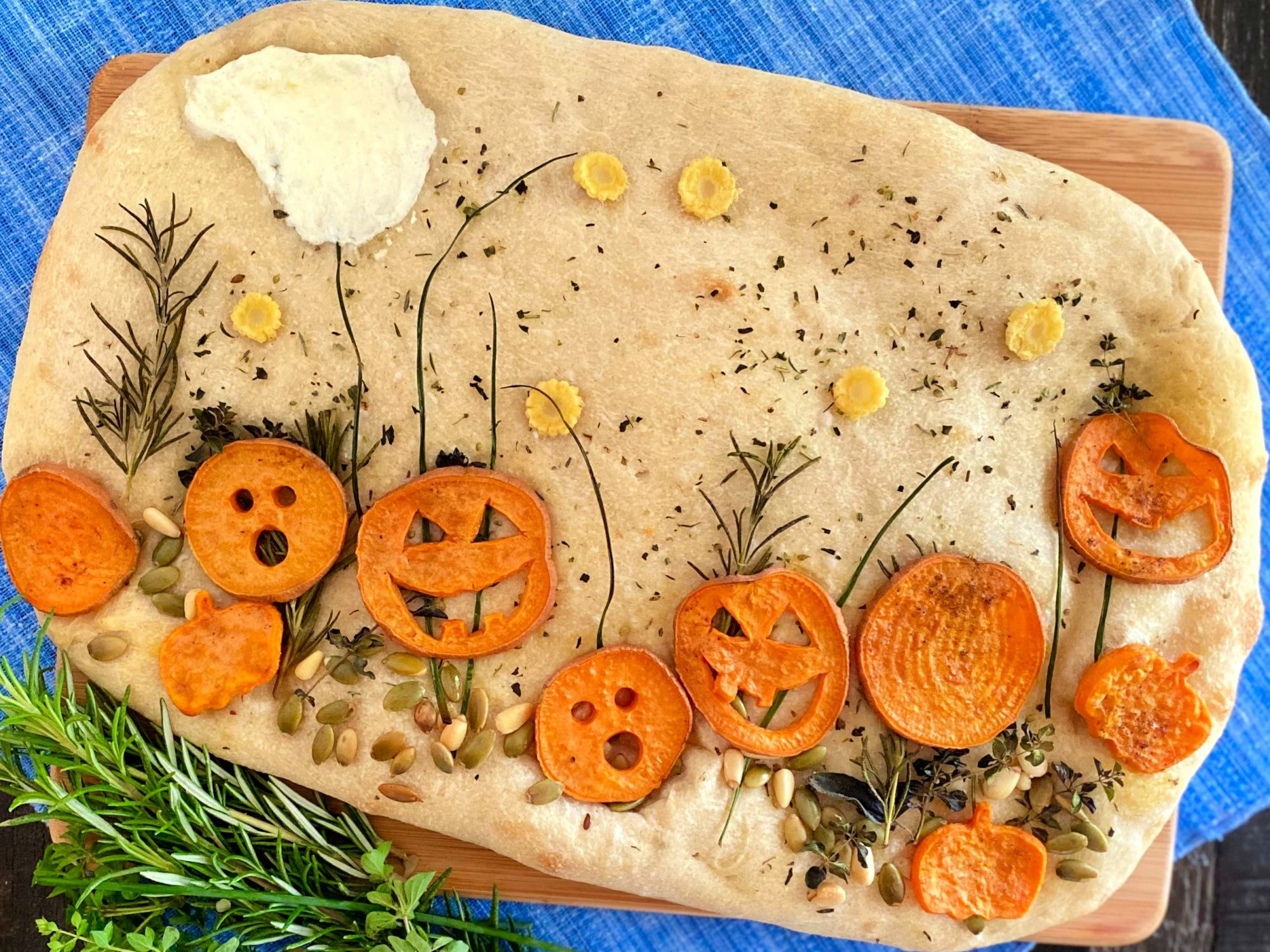 focaccia decorated like a pumpkin patch with yam slices for pumpkins