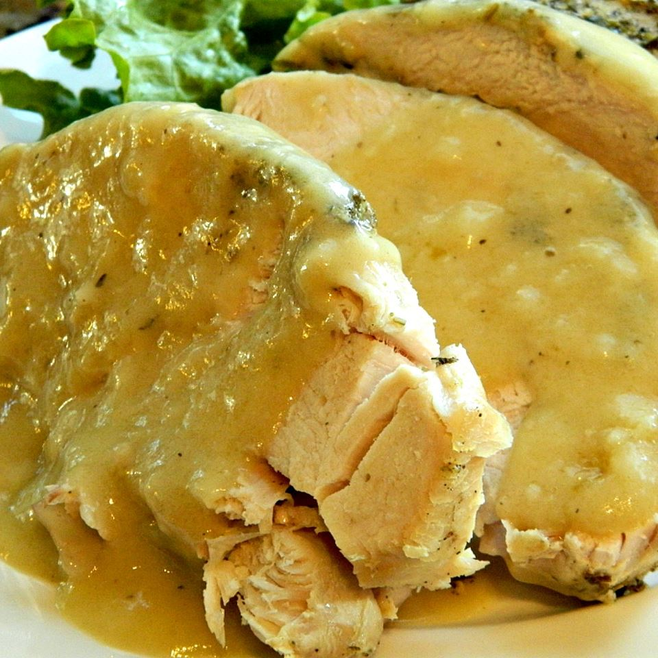 sliced roasted turkey breast with gravy on a platter