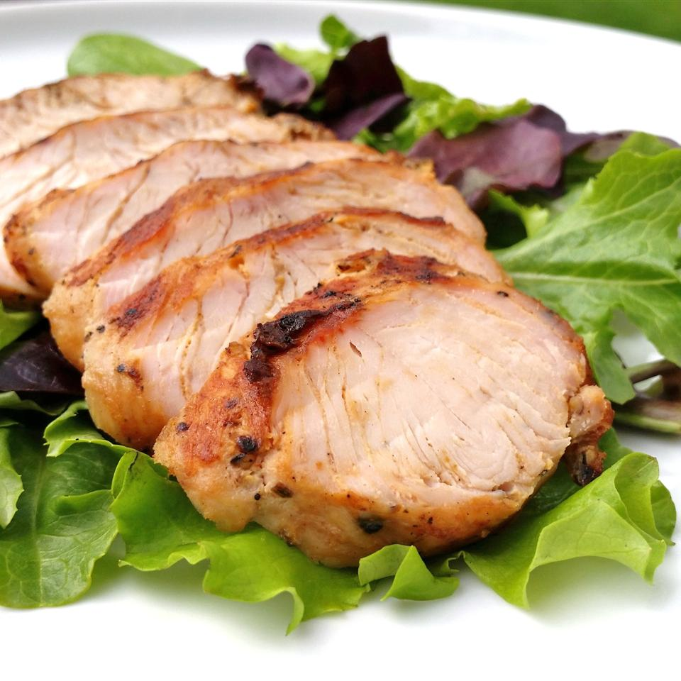 sliced marinated and grilled turkey breast on a bed of fresh lettuces