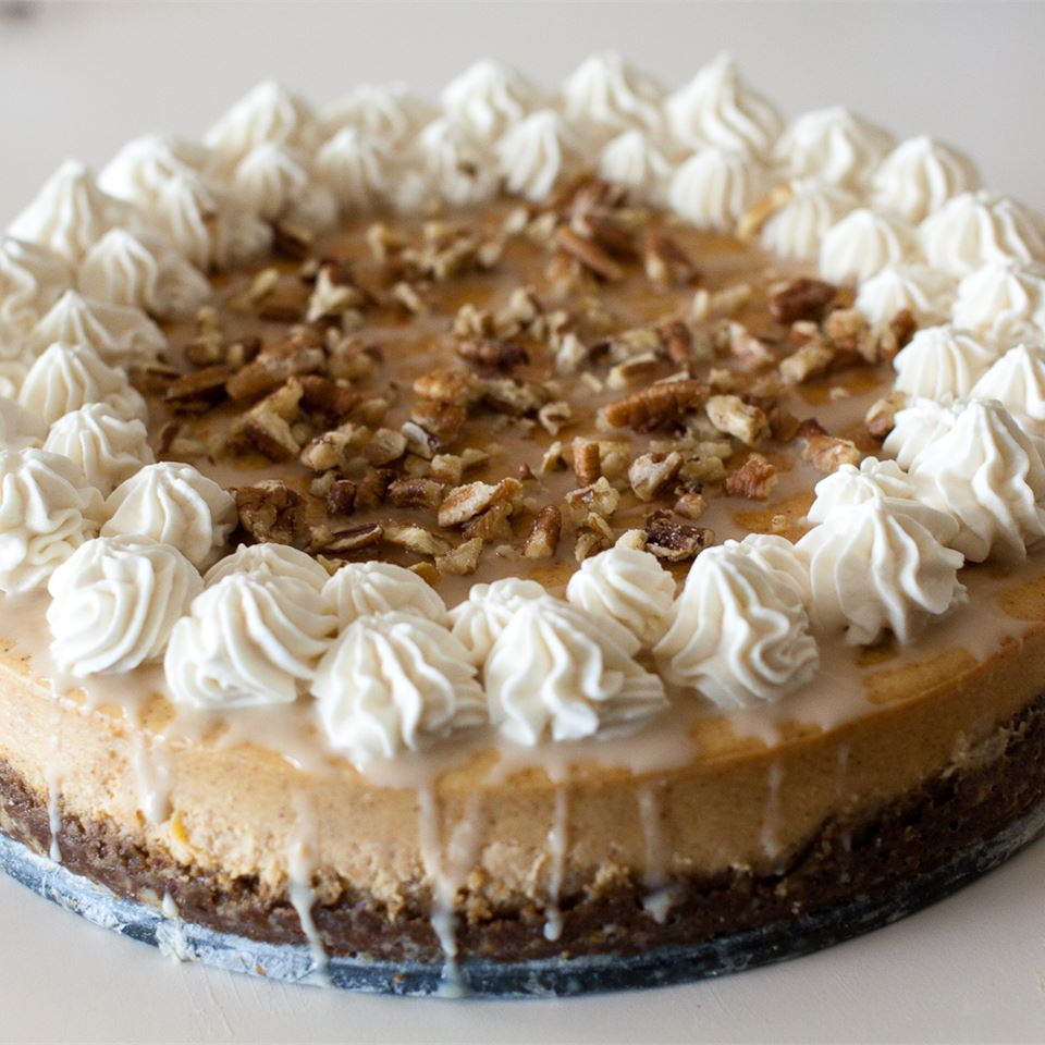 pumpkin cheesecake with whipped cream and chopped nuts