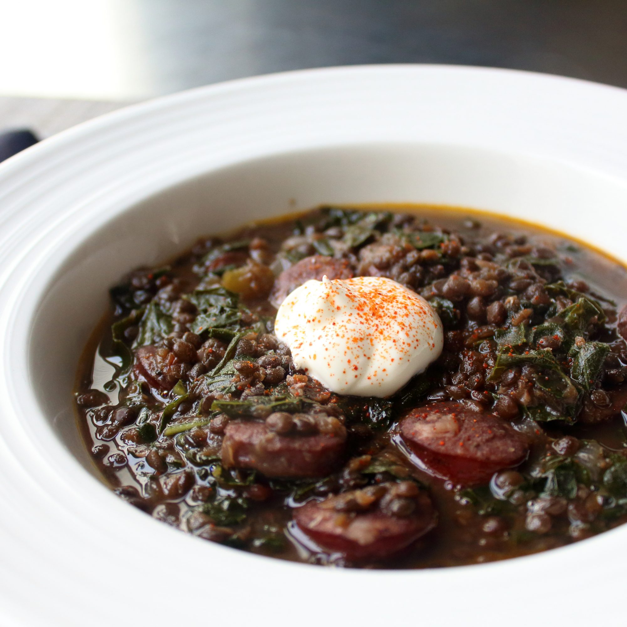 Black Lentil Stew with Sausage and Kale in a white bowl with a dollop of sour cream