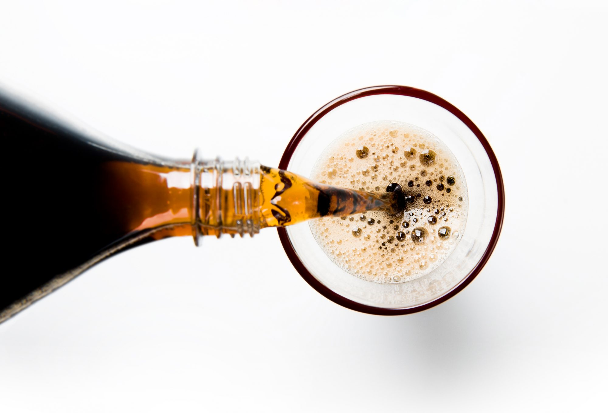A glass of cola being poured into a glass