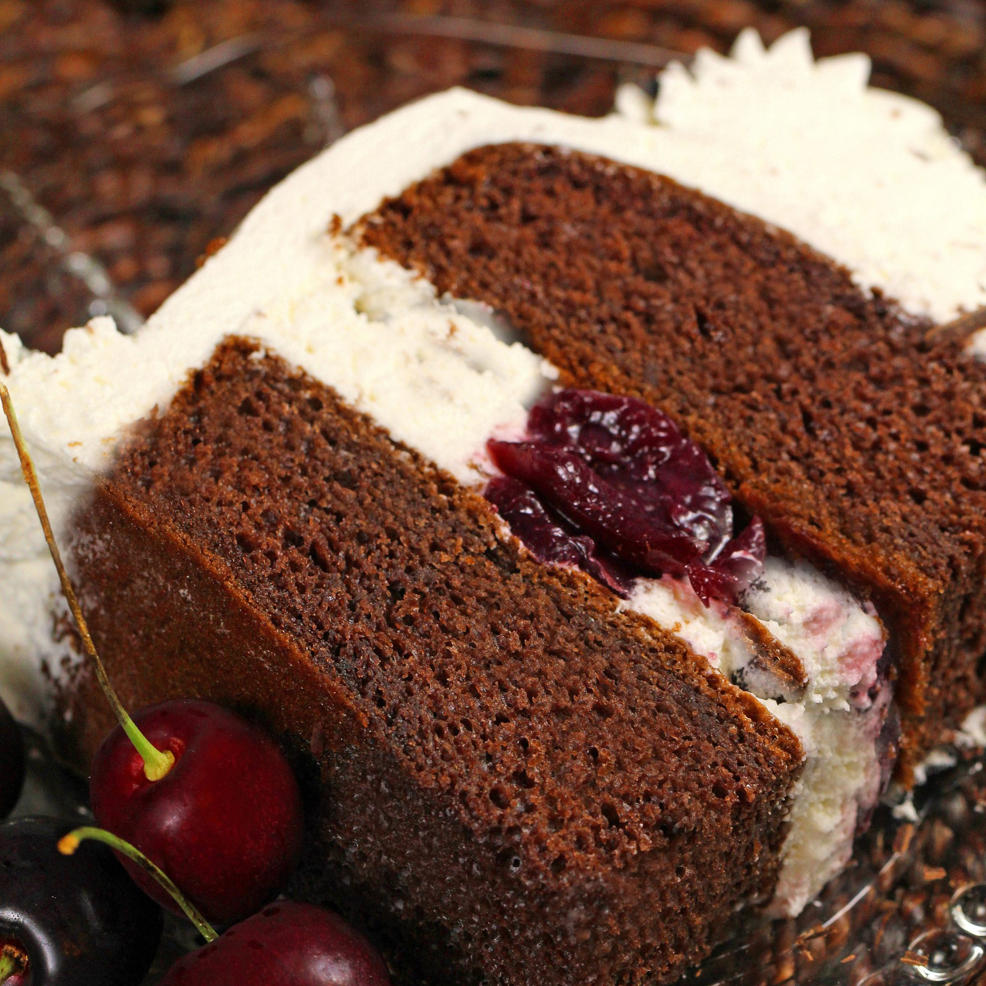 a closeup view of a slice of Black Forest cake with a layer of whipped cream and a cherry in the center, frosted with whipped cream