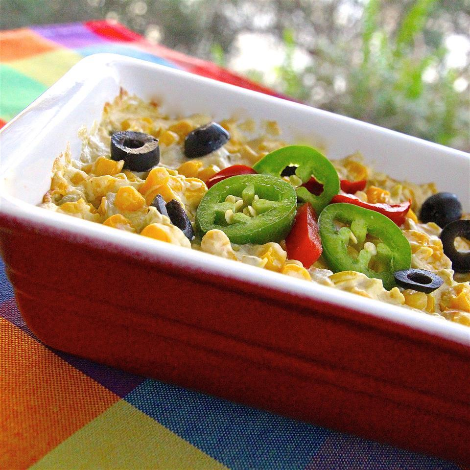 creamed corn with jalapenos and black olives in a red dish