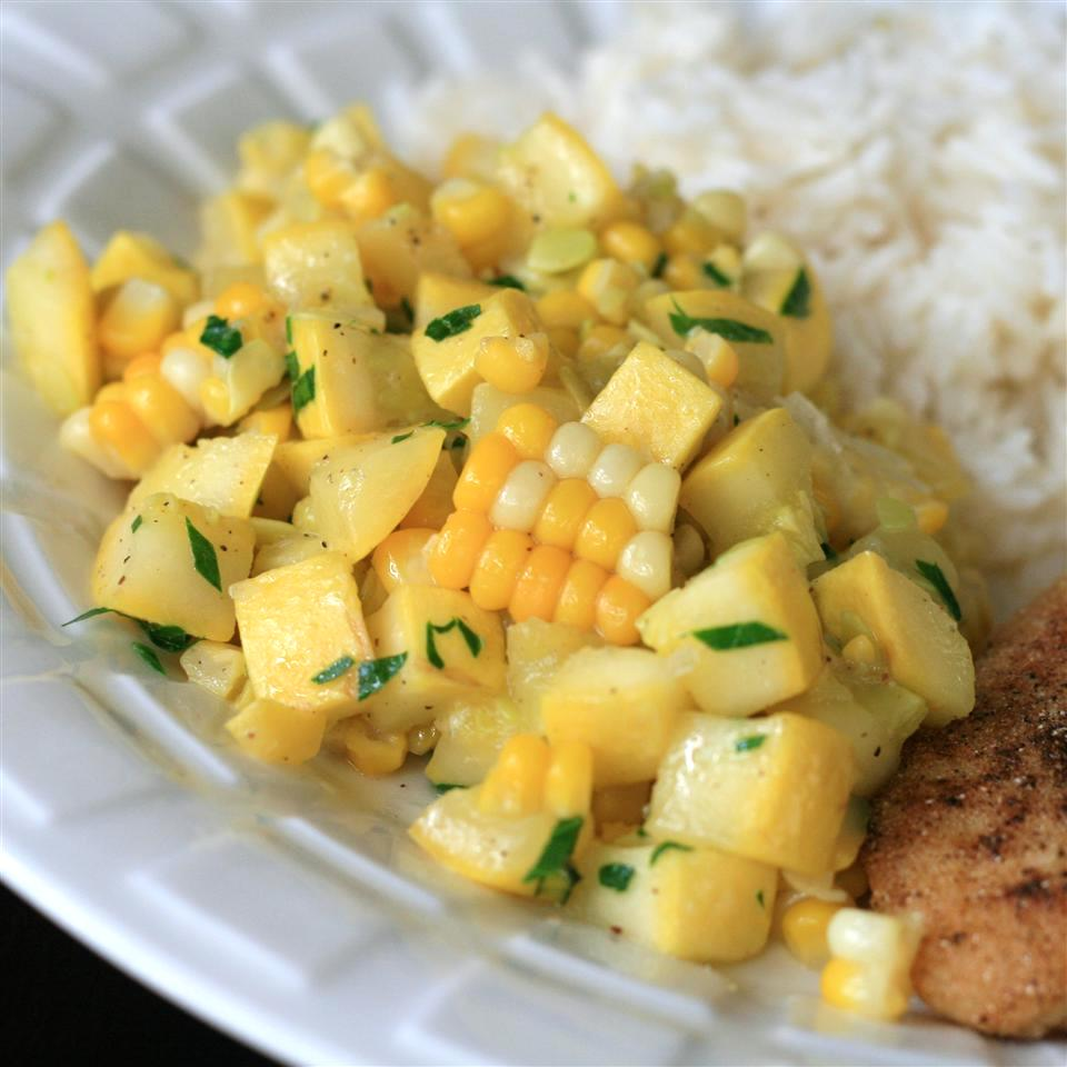 yellow squash and corn on a white plate with rice