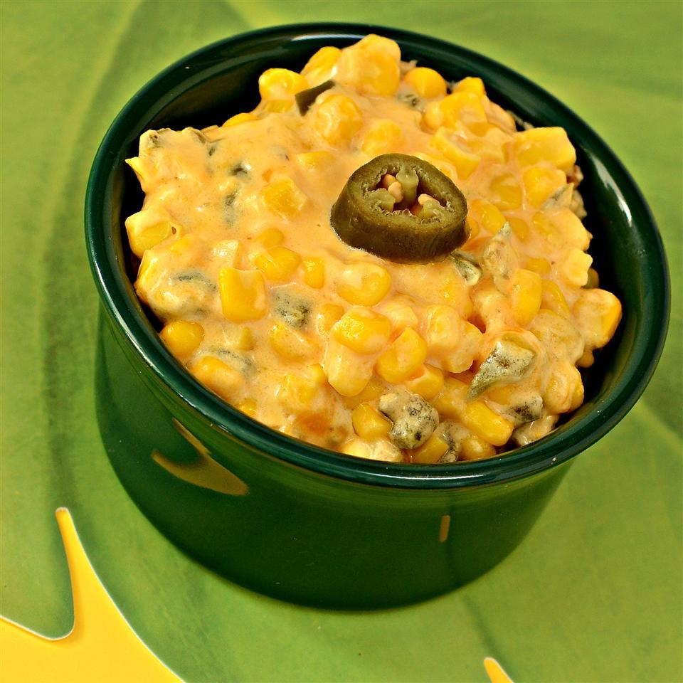 Creamed corn topped with a jalapeno in a green dish
