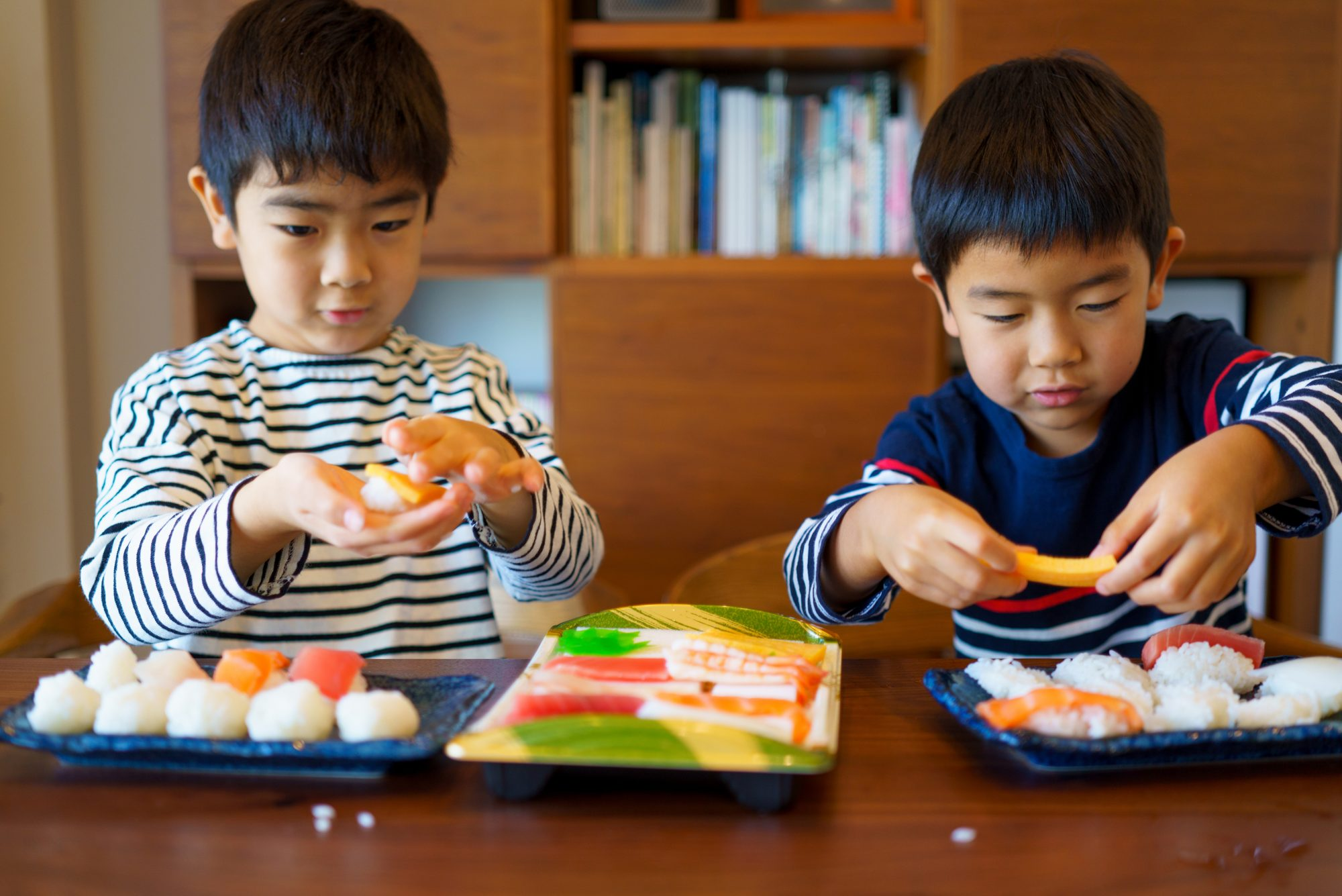 Two boys making sushi at the dinner table