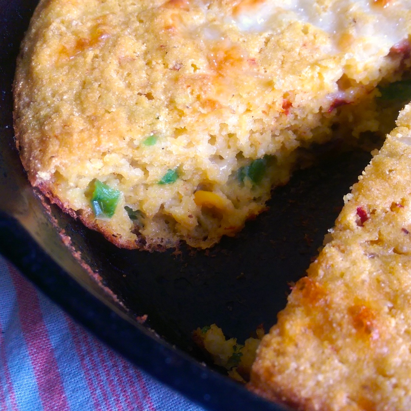 cornbread in a cast iron skillet with a slice cut out