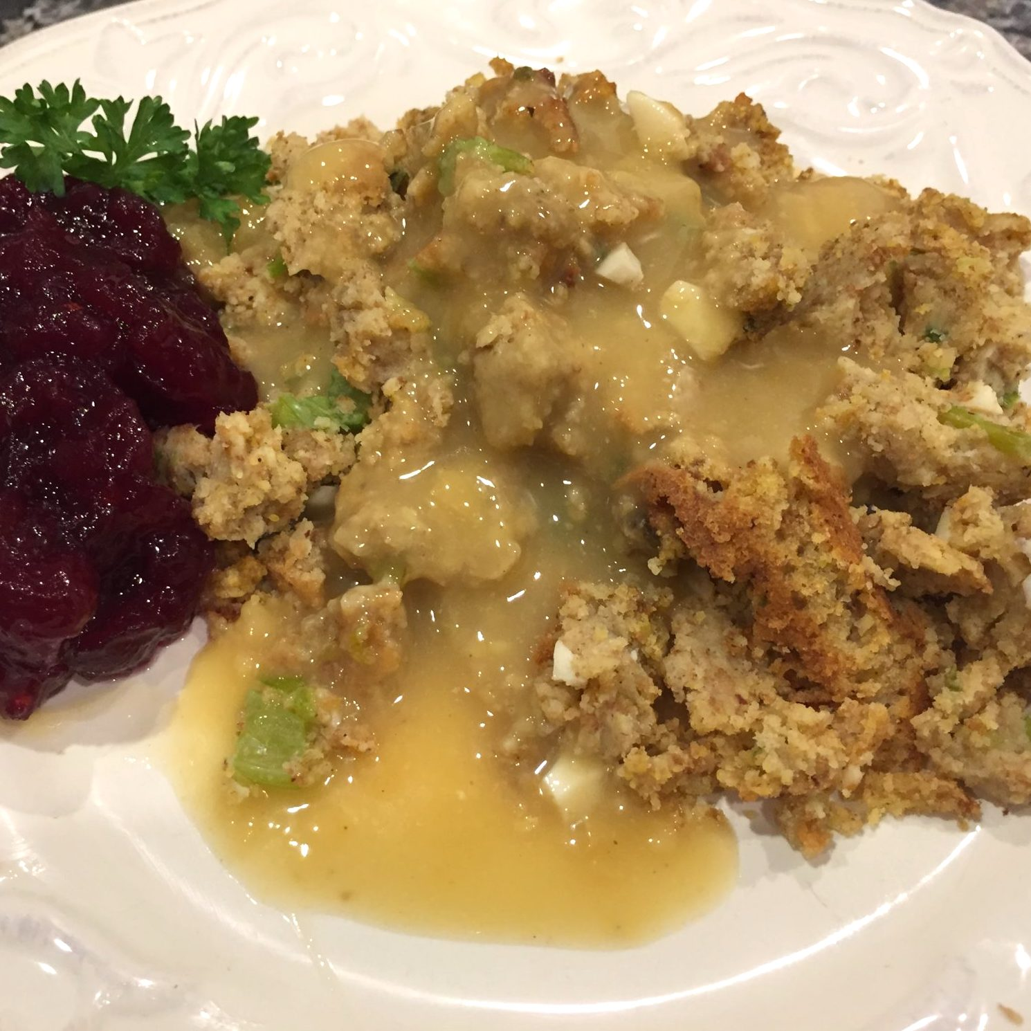plate of cranberry sauce and Grandma's Corn Bread Dressing with gravy