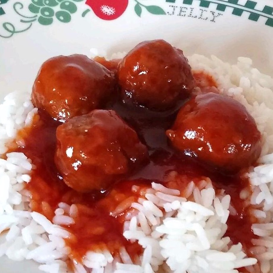 cocktail meatballs in red sauce over rice