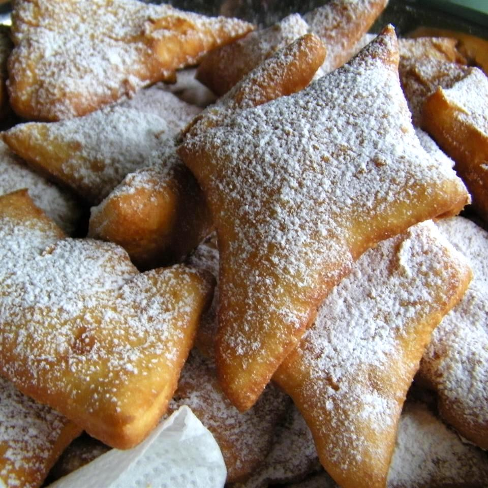 stack of beignets topped with powdered sugar