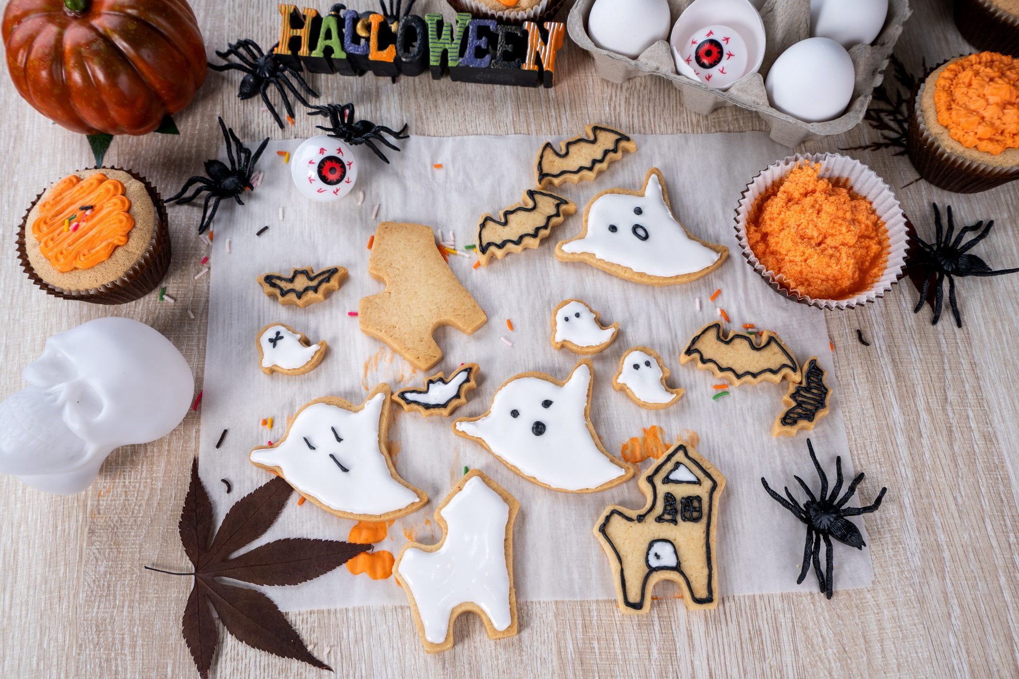 Fresh homemade decorating halloween dessert with ghost, creeping spider, bat, haunted castle and horrifying eyeball on wooden background, copy space - stock photo