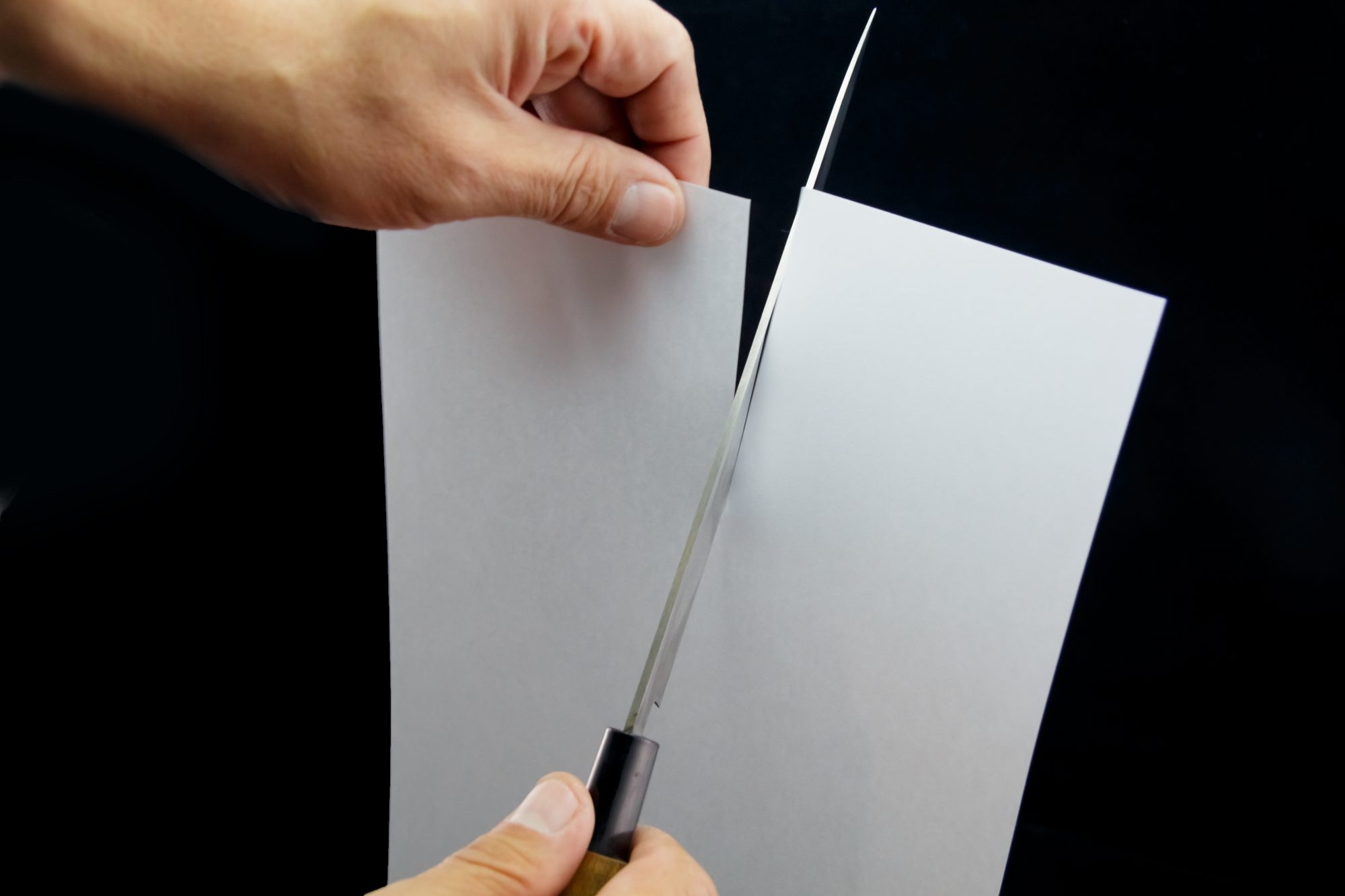 Person cutting a piece of paper with sharp knife