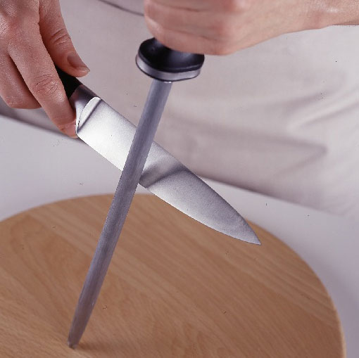 Person using honing rod to hone knife