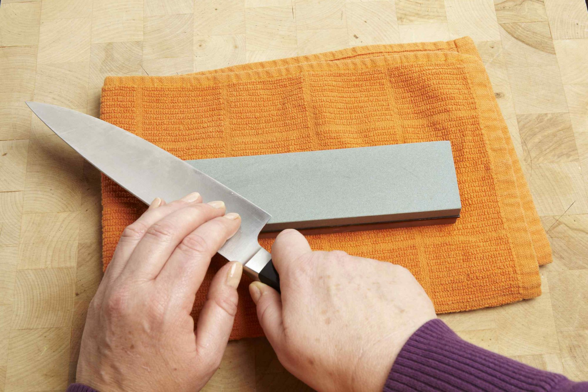 Person with chef's knife being sharpened on sharpening stone