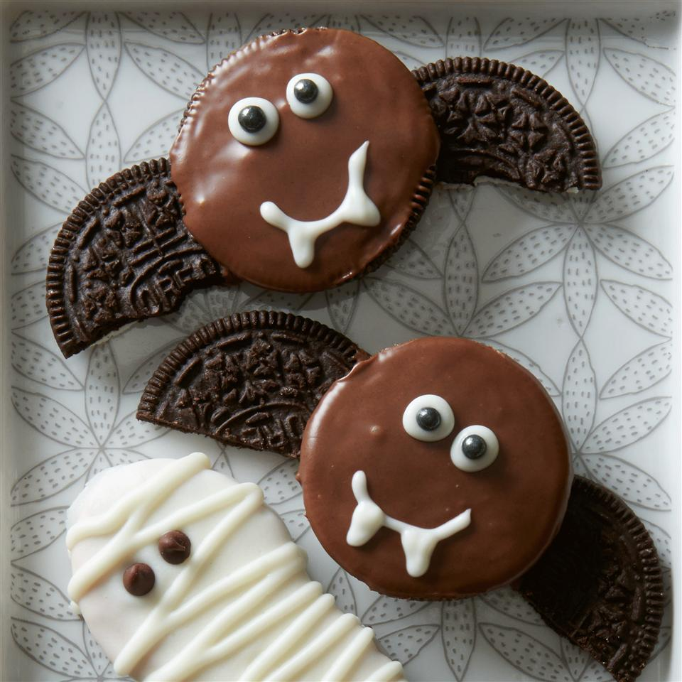 """Two chocolate-dipped Oreos decorated to look like baths with Oreo """"wings"""", next to a white chocolate-dipped Nutter Butter mummy"""