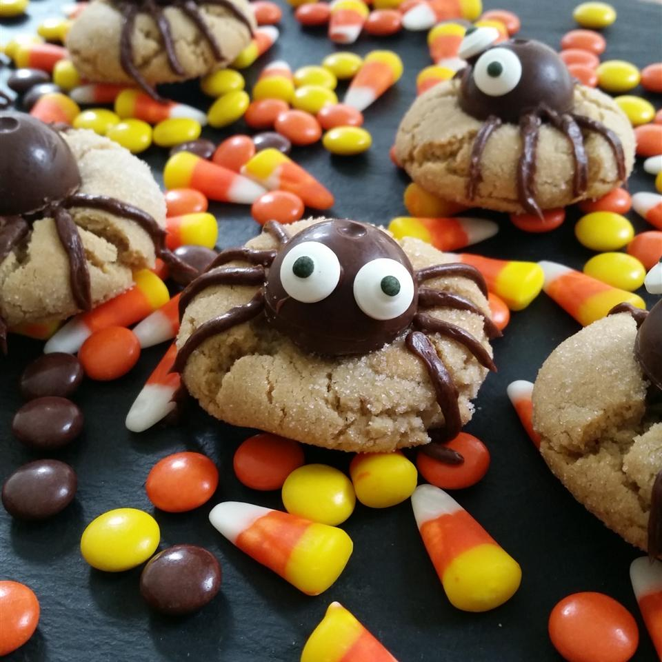 """Peanut butter cookies topped with chocolate candy """"spiders"""" with candy corn in the background"""