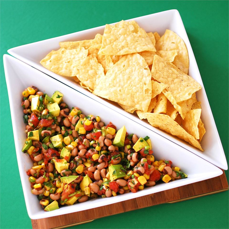 Avocado and Black Eyed Pea Salsa with tortilla chips in a white bowl