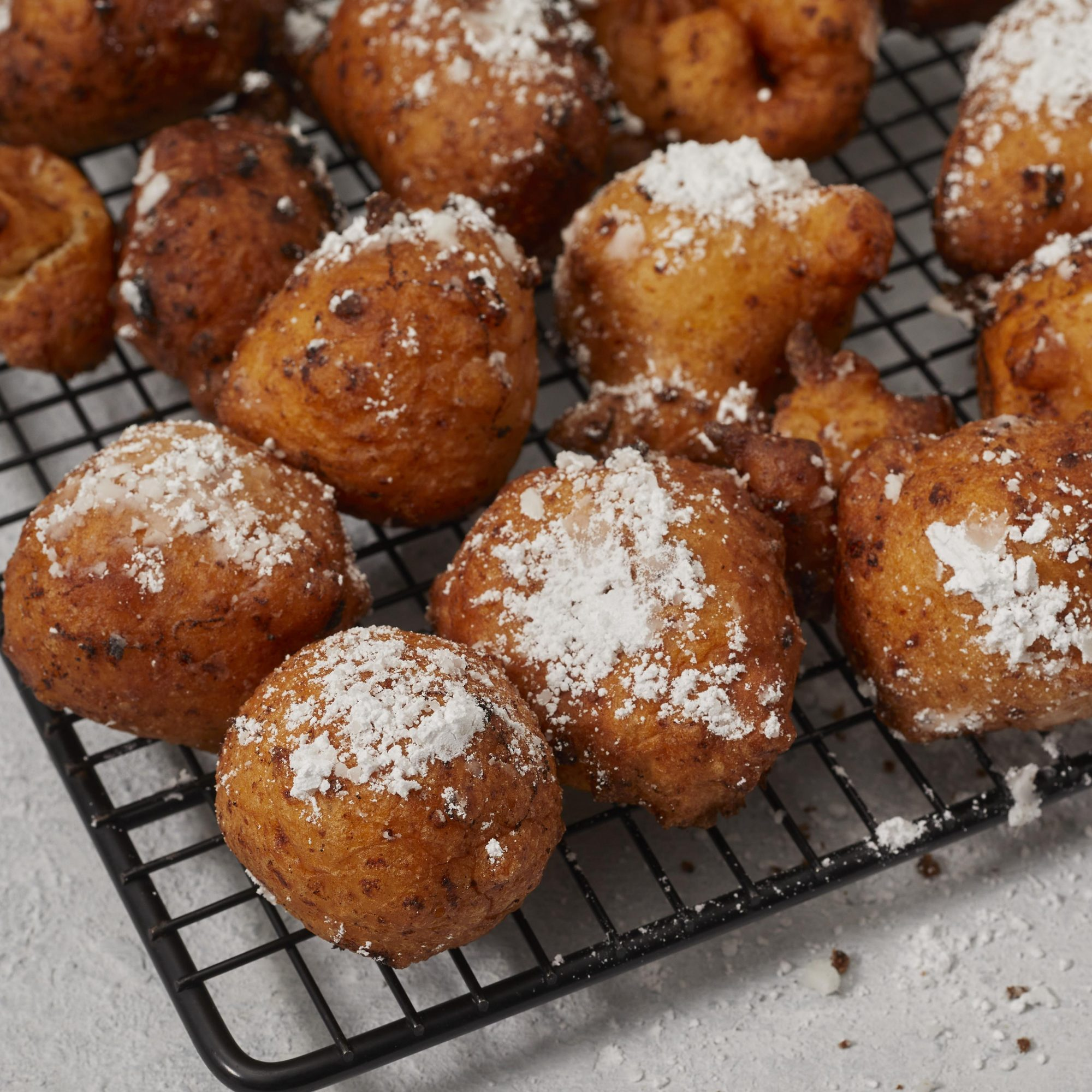 Cheese fritters on a cooling rack, dusted with confectioners' sugar