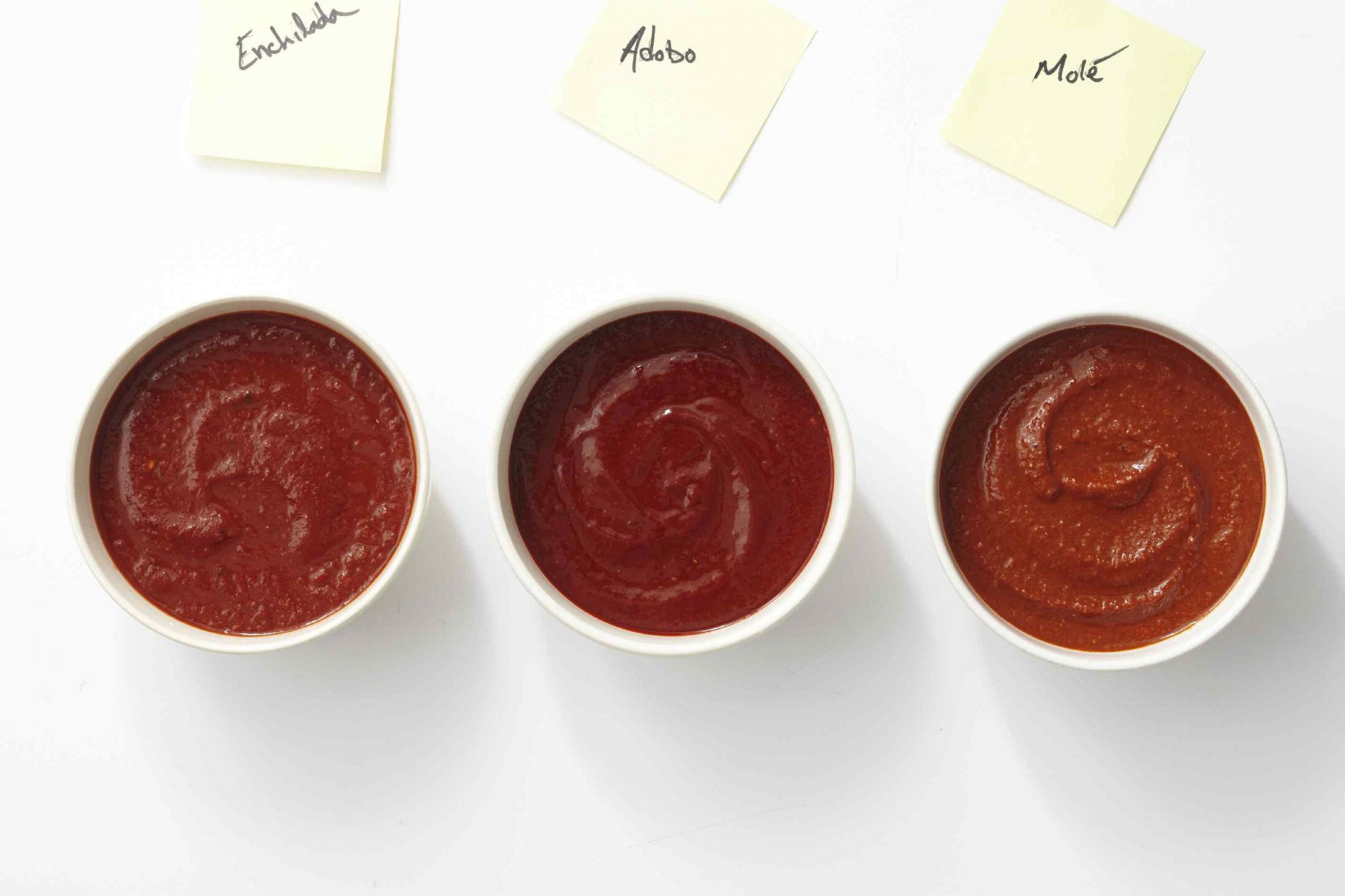 Enchilada sauce, adobo sauce, and mole sauce in bowls