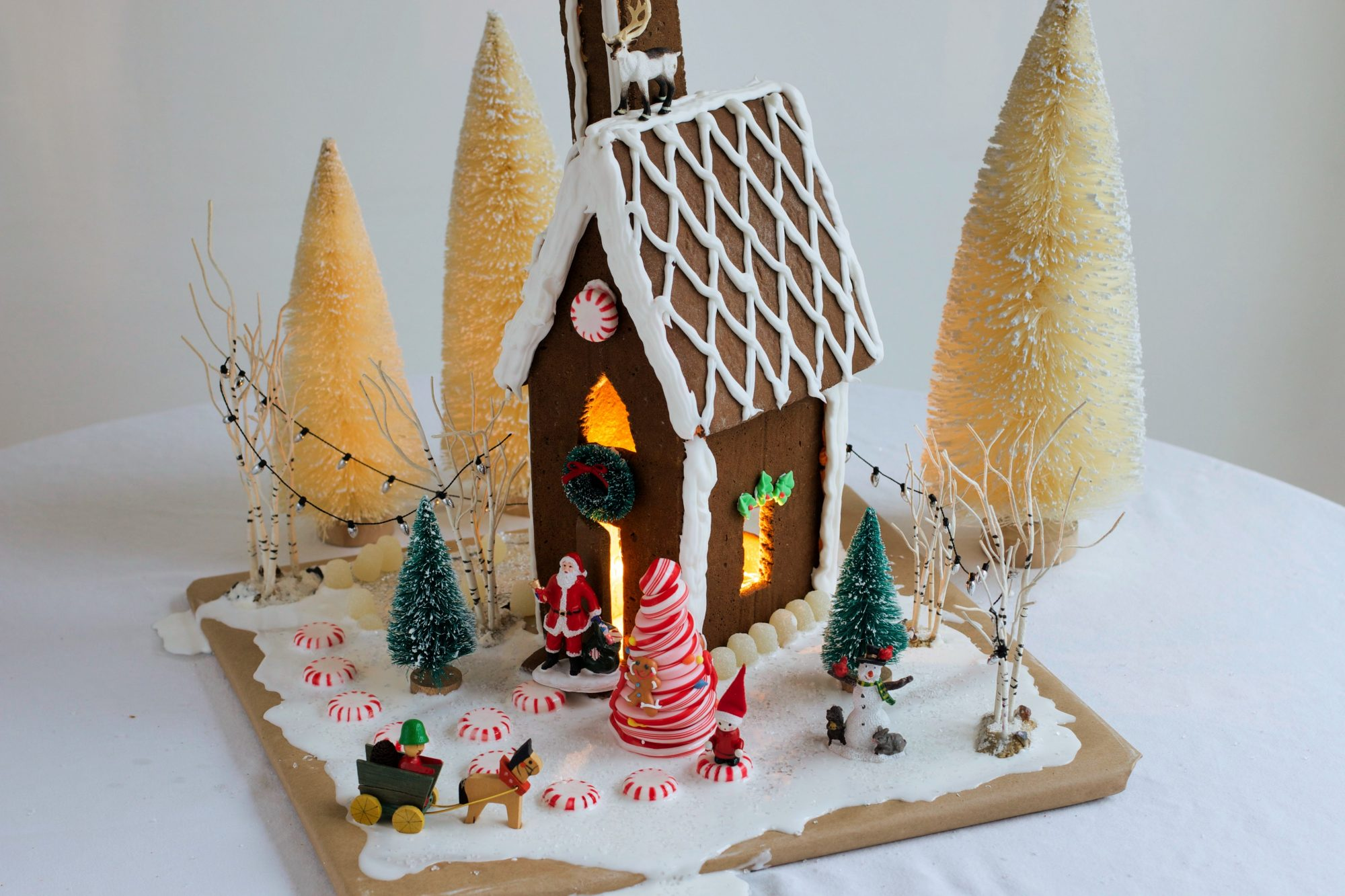 homemade gingerbread house decorated for christmas with candy, toys, and lights