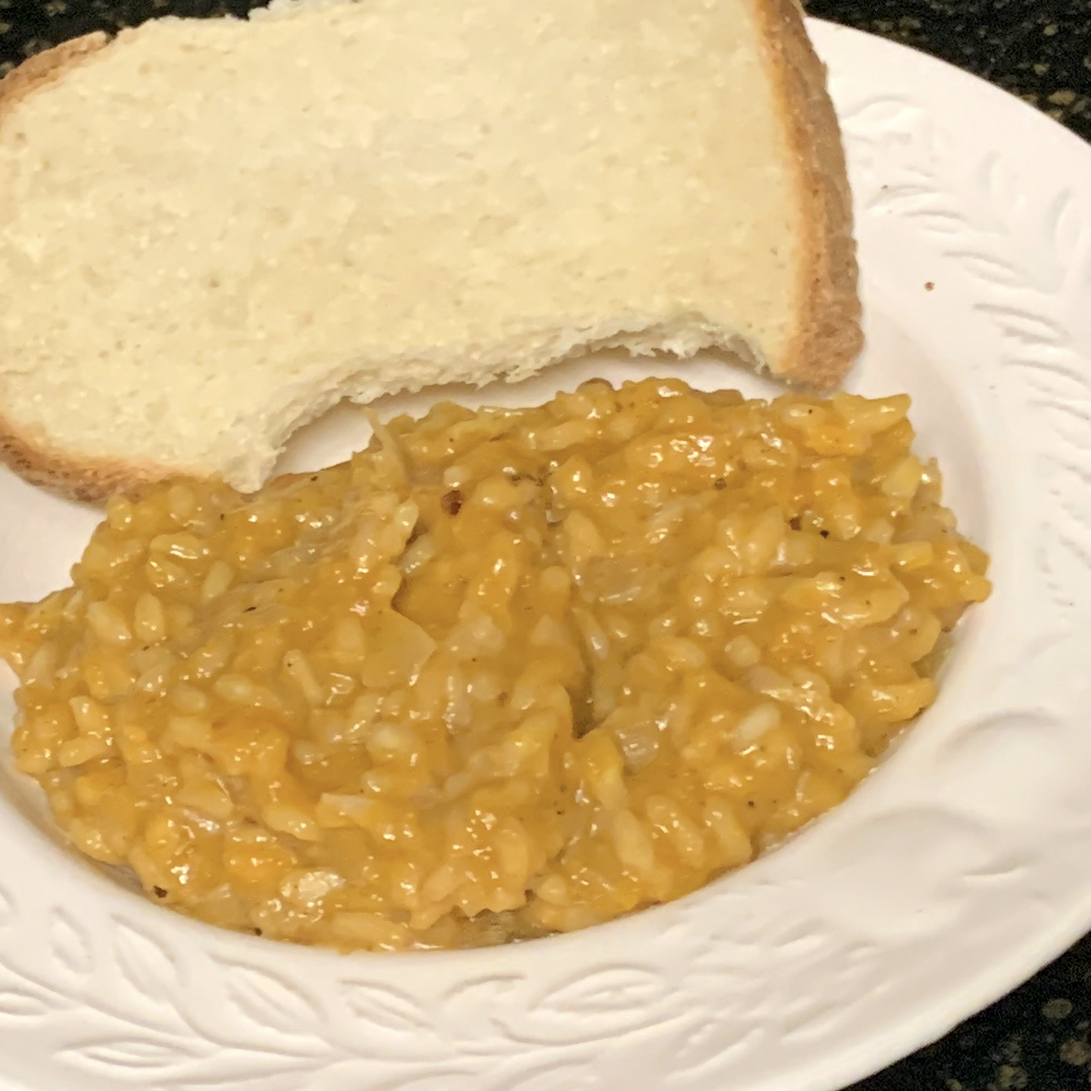 pumpkin risotto with bread on a white plate