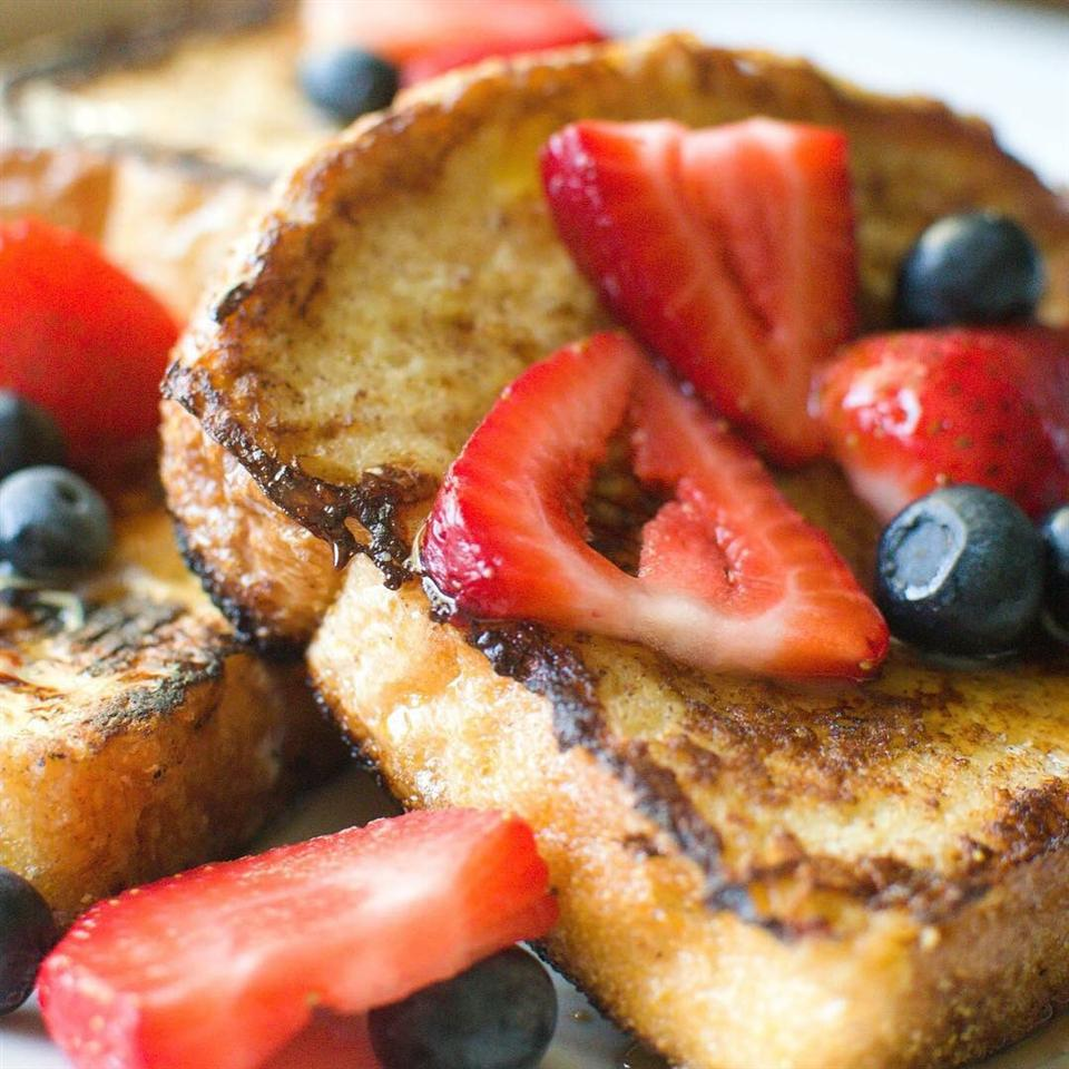 plate of french toast topped with syrup and fresh berries