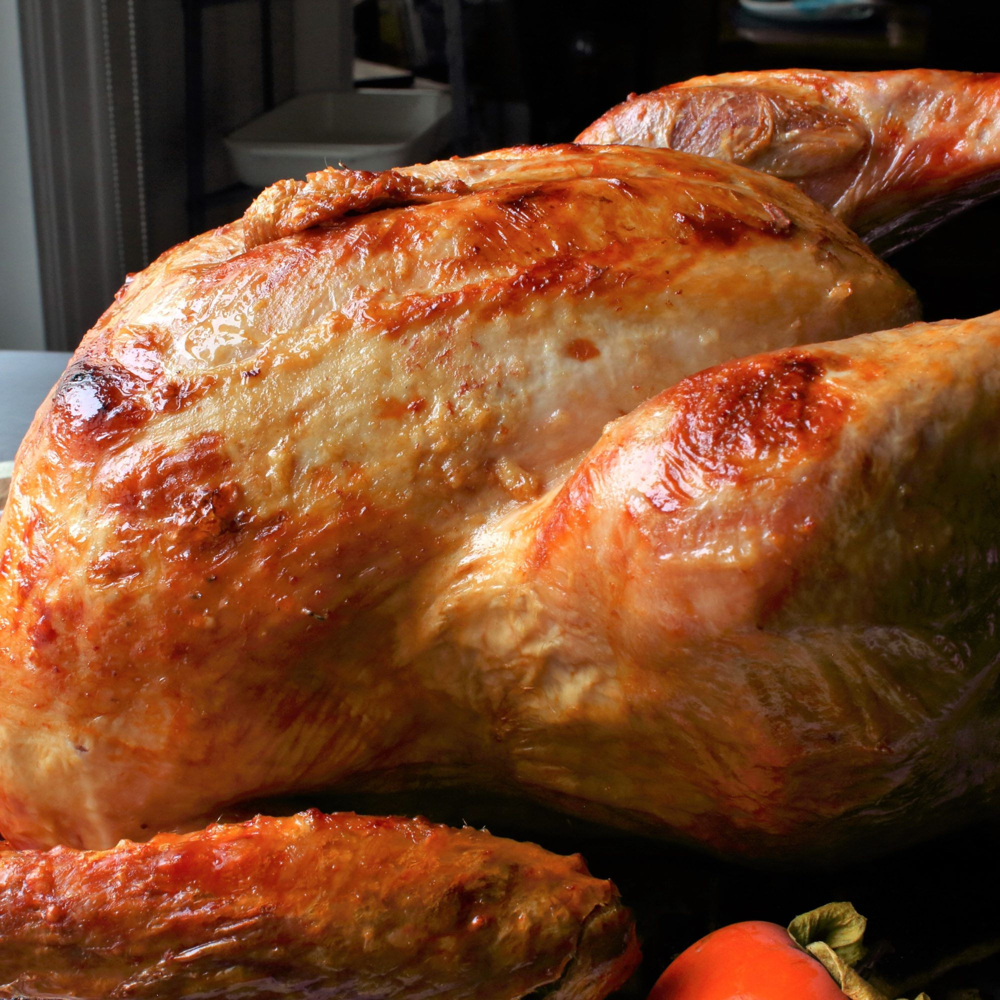 a roast turkey on a platter with fresh persimmons